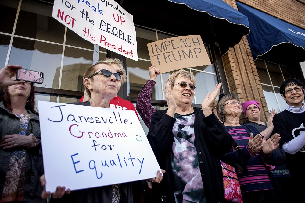 Protesters hold signs outside of House Speaker Paul Ryan's office on Main Street in downtown Janesville, Wis., Wednesday, Feb. 22, 2017. (Angela Major/The Janesville Gazette via AP)