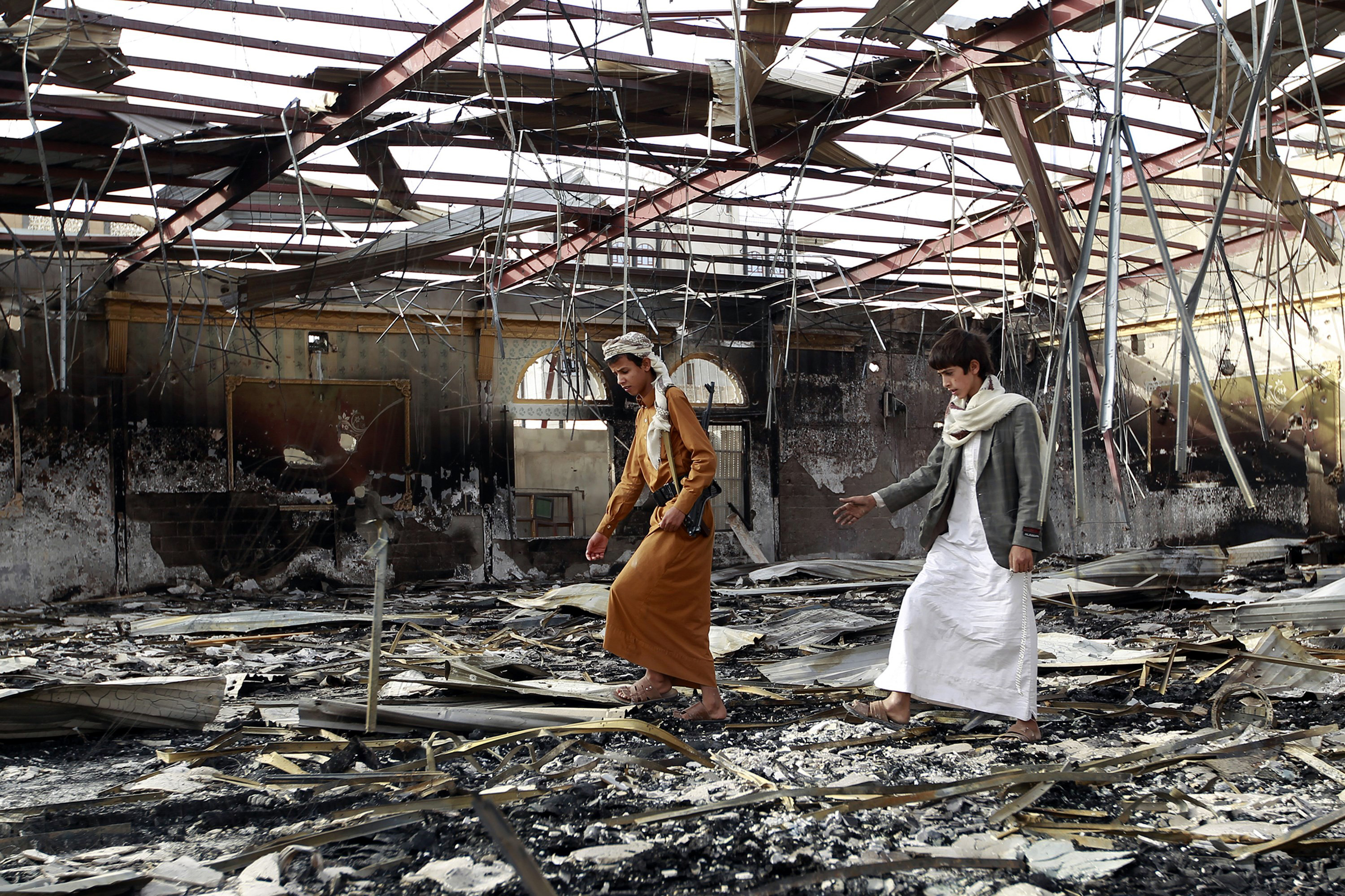 Armed Yemenis walk on the debris at a wedding hall which was reportedly hit by a Saudi-led coalition air strike in the capital Sanaa, on July 10, 2015, a few hours before a humanitarian pause was to take effect. The humanitarian pause in the war in Yemen will be
