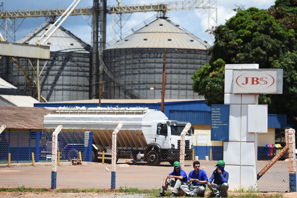 "Workers take a rest at the entrence of JBS-Friboi chicken processing plant, in Samambaia, Federal District, Brazil on March 17, 2017.<br /><br /><br /><br /><br /> Brazilian Federal police have dismantled, after two years of running the ""weak flesh"" operation, a vast network of adulterated food, involving major meat processing plants and inspectors who accepted bribes to approve products in bad condition for domestic consumption and exportation.  / AFP PHOTO / EVARISTO SA        (Photo credit should read EVARISTO SA/AFP/Getty Images)"