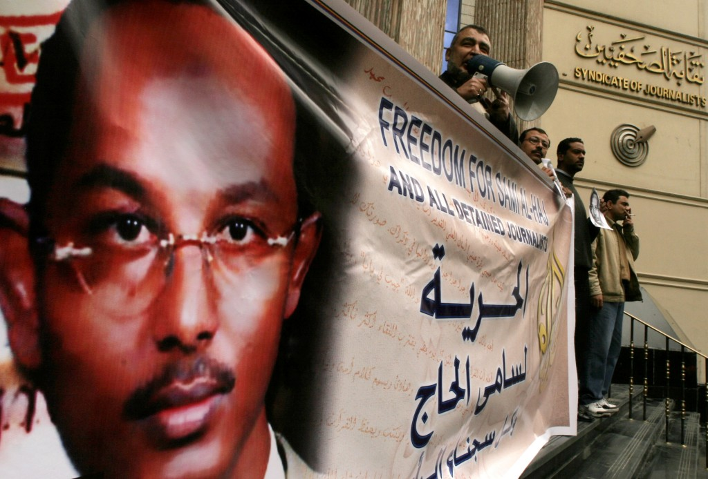 **  FILE ** Egyptian journalists hold a banner supporting Al Jazeera cameraman Sami al-Haj, a Sudanese national who was arrested by the US military while working for Al Jazeera during the US invasion of Afghanistan in 2001, as they call for his freedom during a protest in front of their syndicate in Cairo, Egypt, in this March 15, 2007 file photo.  According to an annual survey by the Committee to Protect Journalists, at least 127 journalists worldwide are behind bars, and one in six have never been publicly charged with a crime. The group cited  Sami al-Haj, who has been jailed for five years at the military prison camp in Guantanamo Bay, Cuba, as one of two journalists who have been held without charges by the United States. (AP Photo/Amr Nabil,File)