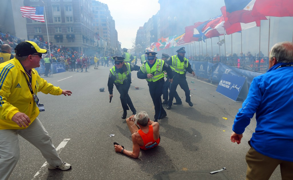 BOSTON - APRIL 15: Police officers with their guns drawn hear the second explosion down the street. The first explosion knocked down 78-year-old US marathon runner Bill Iffrig at the finish line of the 117th Boston Marathon. (Photo by John Tlumacki/The Boston Globe via Getty Images)
