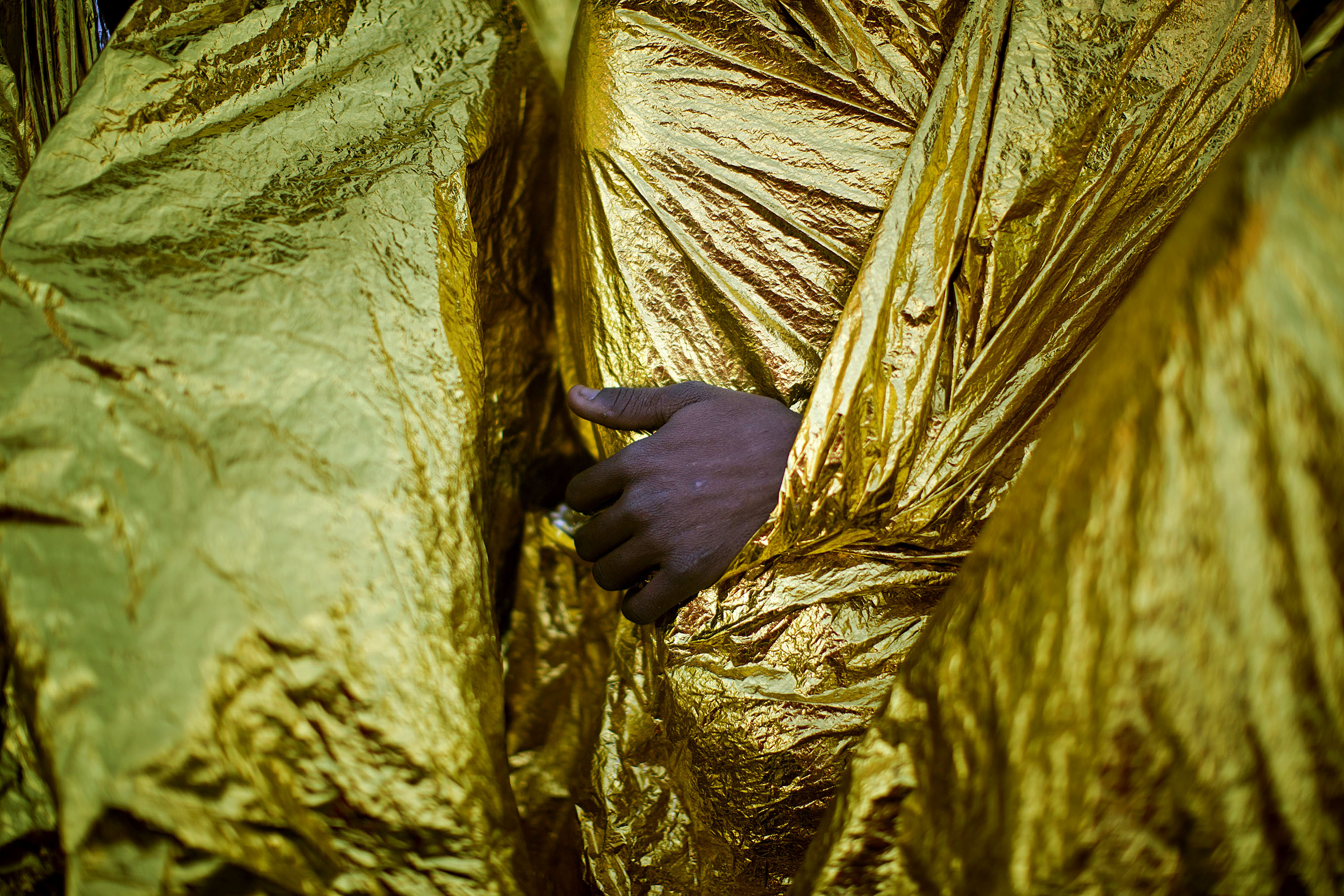 The hand of an Sub-Saharan migrant is seen outside the blanket as men sit on the deck of the Golfo Azzurro rescue vessel after arriving at the port of Messina, in Italy, with more than 299 migrants aboard the ship rescued by members of Proactive Open Arms NGO, on Sunday, Jan. 29, 2017. (AP Photo/Emilio Morenatti)