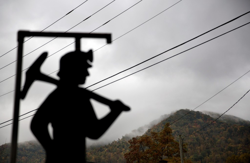 In this Oct. 16, 2014 photo, fog hovers over a mountaintop as a cut out of a coal miner stands at a memorial to local miners killed on the job in Cumberland, Ky. For over a century, life in Central Appalachia has been largely defined by the ups and downs of the coal industry. Through all the bust years, there was always the promise of another boom. Until now. There is a growing sense in these mountains that this downturn is different, deeper. That for a variety of reasons, economic, environmental, political, coal mining will not rebound this time. As recently as the late 1970s, there were more than 350 mines operating at any given time in Harlan County. Today, it's around 40. (AP Photo/David Goldman)