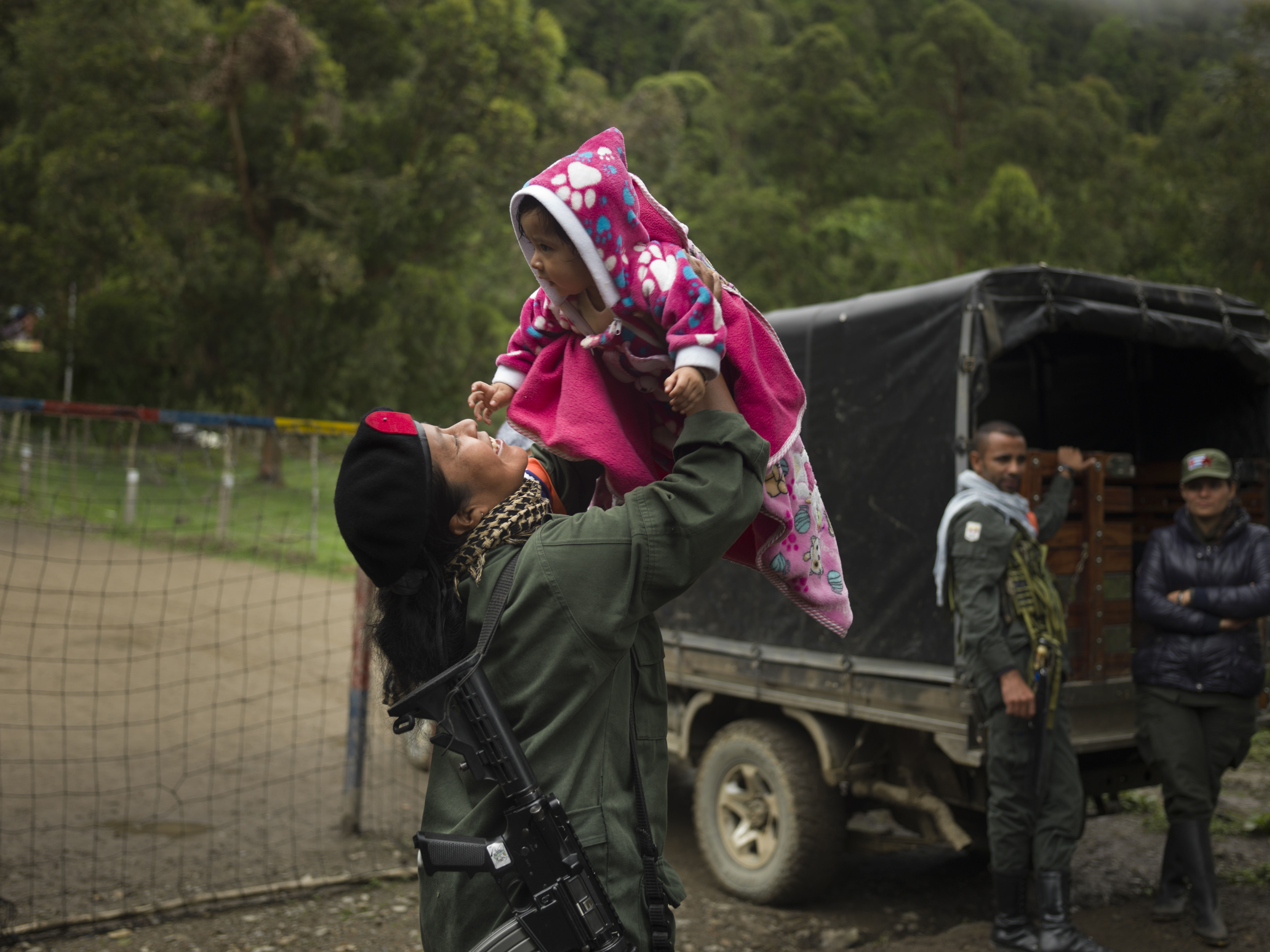 COLOMBIA. 2017. A fighter playing with a comrade's child. For the first time since FARC's formation, female members are allowed to keep their babies with the permission of their commander.