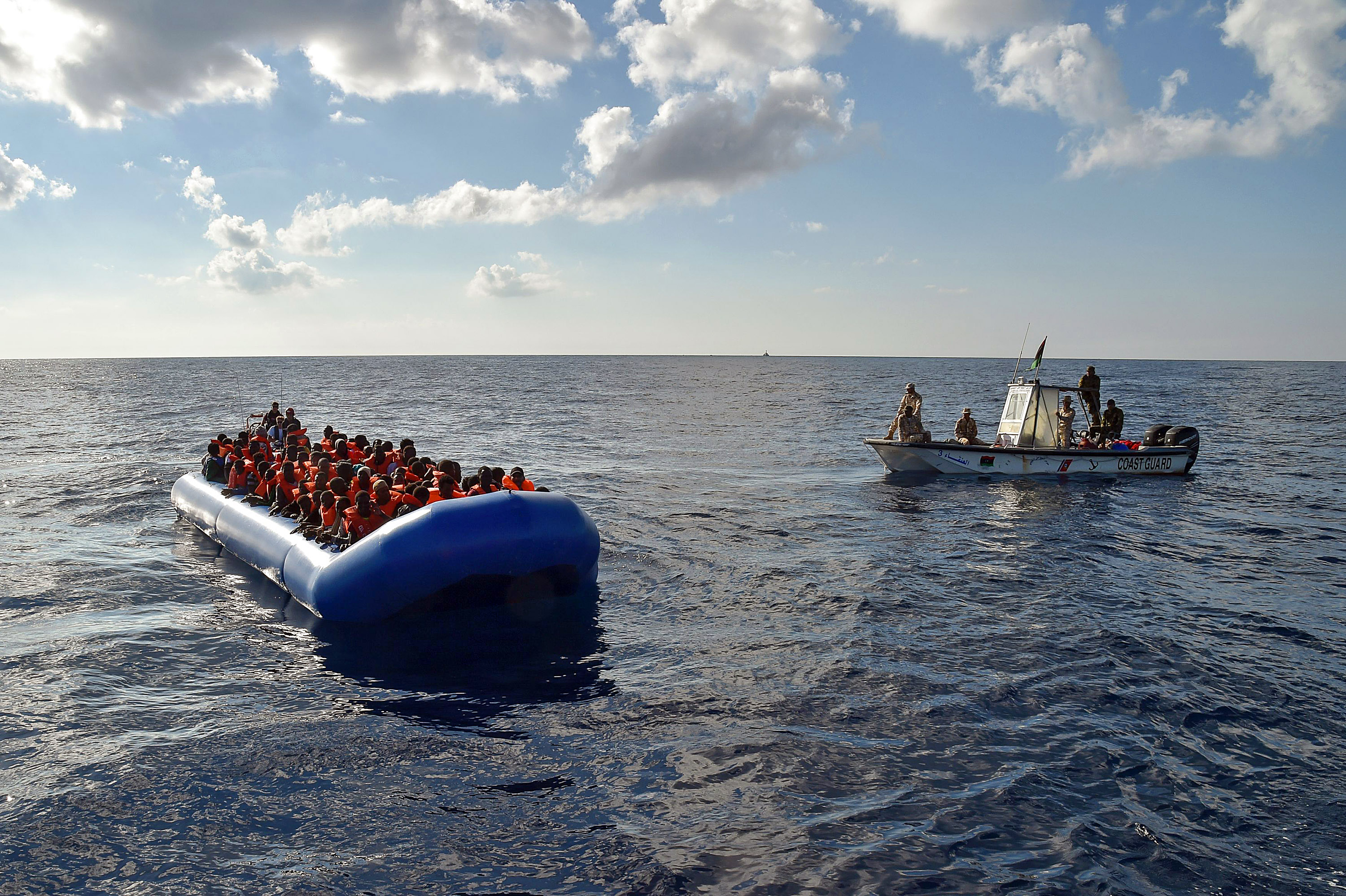 """TOPSHOT - Migrants and refugees sit on a rubber boat as the Libyan coastguards patrol, during a rescue operation of the Topaz Responder, a rescue ship run by Maltese NGO """"Moas"""" and the Italian Red Cross, on November 4, 2016 off th Libyan coast.Around 750 migrants were rescued across the Mediterranean Thursday by the Italian coast guard, a Frontex ship, a Save The Children vessel, German NGO Jugend Rettet's Iuventa and two boats run by the Malta-based MOAS (Migrant Offshore Aid Station). But at least 110 migrants are feared drowned after they were forced at gunpoint to set sail from Libya, while many more may have died in a separate shipwreck, survivors said. / AFP / ANDREAS SOLARO (Photo credit should read ANDREAS SOLARO/AFP/Getty Images)"""