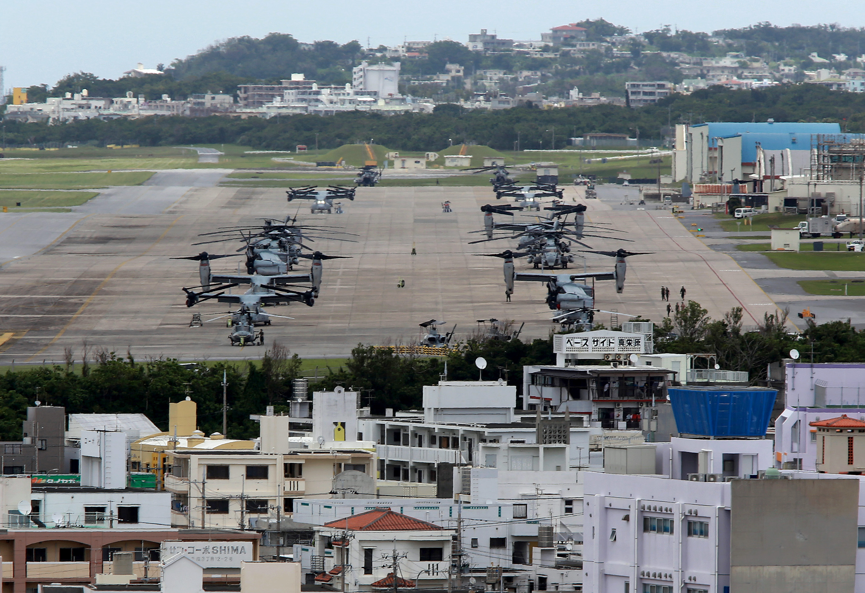 epa04756429 US Marine Corps MV-22 Osprey aircrafts are sitting on the tarmac at US Marine Corps Air Station Futenma surrounded by overcrowded residential areas in Ginowan on Okinawa Island, southwestern Japan, 19 May 2015. Japanese government just announced on May 12 that CV-22 Ospreys would be deployed to the U.S. Air Force's Yokota base on the outskirt of Tokyo. CV-22 Ospreys is for special operations forces, engage in low-altitude and nighttime flights, and the accident rate is three times higher than Marines MV-22 Ospreys. Japanese four local cities' leaders in Tokyo surrounding US Air Force's Yokota Base have expressed deep concern over the deployment of CV-22 Ospreys in 2017, as Pentagon announced on 18 May 2015 it had no plan to change Osprey operations in Japan after a CV-22 Osprey crash in Hawaii killing one and injuring 21 on last weekend.  EPA/HITOSHI MAESHIRO