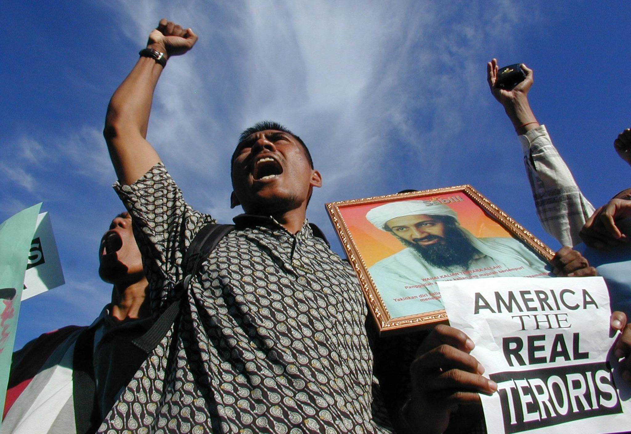 "BANDA ACEH, INDONESIA:  A Muslim protestor holding a portrait of Saudi-dissident Osama bin Laden shout ""Allah Akbar"" during a protest in front of Baiturrahman mosque, Banda Aceh, 10 October 2001. The demonstrators are protesting against the US-led military strikes against Afghanistan.       AFP PHOTO (Photo credit should read AFP/Getty Images)"