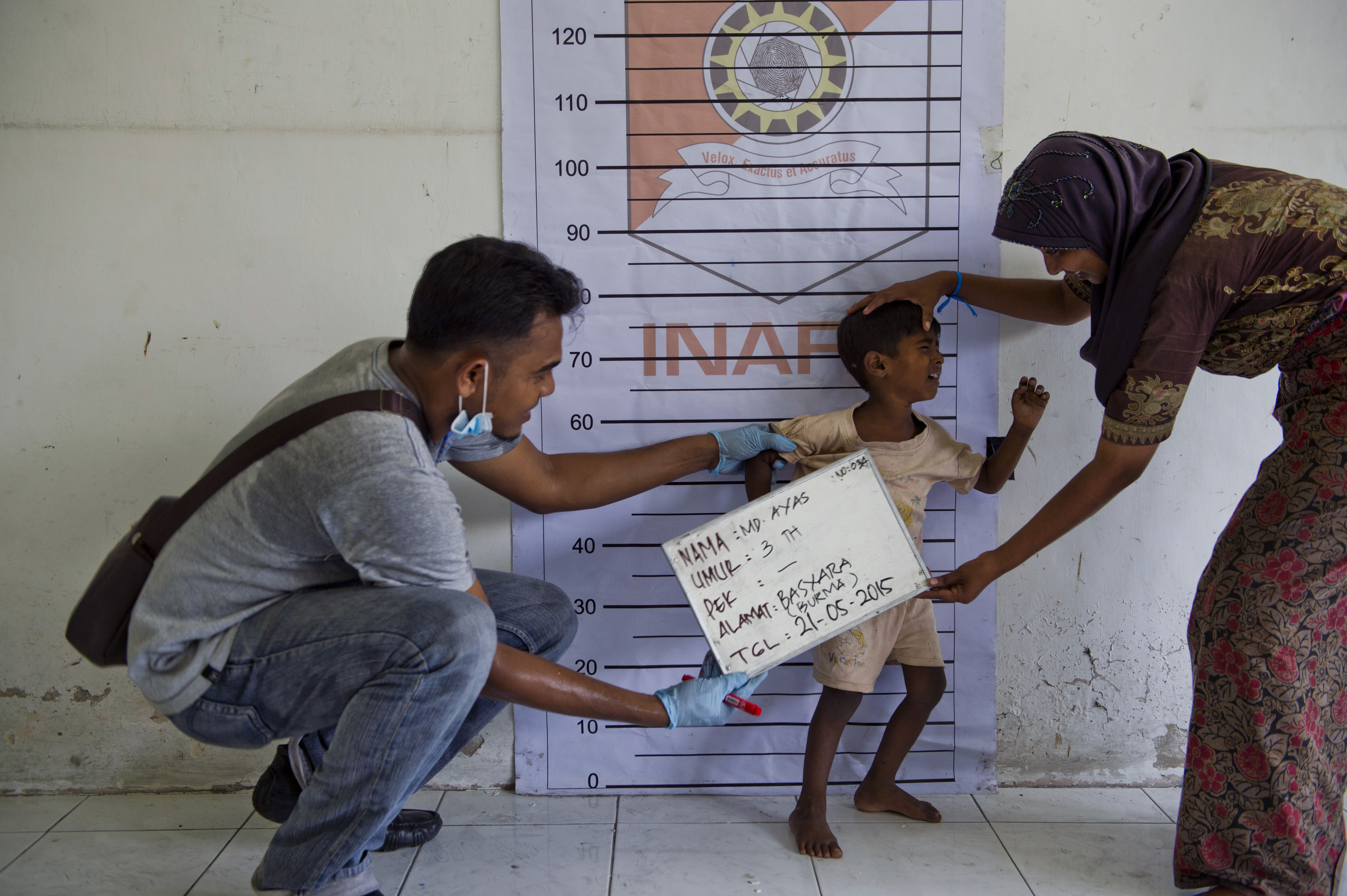 "To go with ""SEAsia migrants Indonesia"", Focus by Olivia RondonuwuIn this picture taken on May 21, 2015, a Rohingya boy (C) from Myanmar is photographed during police identification procedures at a newly set up confinement area in Bayeun, Aceh province after more than 400 Rohingya migrants from Myanmar and Bangladesh were rescued by Indonesian fishermen off the waters of the province on May 20. Boat people who have come ashore in Southeast Asia after harrowing journeys are delighted that Indonesia and Malaysia will give them temporary shelter -- although some were baffled by an offer of sanctuary in a tiny African nation they had never heard of. There was some confusion over an offer from the impoverished West African nation of Gambia to take in all Rohingya migrants as part of its ""sacred duty"" to alleviate the suffering of fellow Muslims. AFP PHOTO / ROMEO GACAD (Photo credit should read ROMEO GACAD/AFP/Getty Images)"