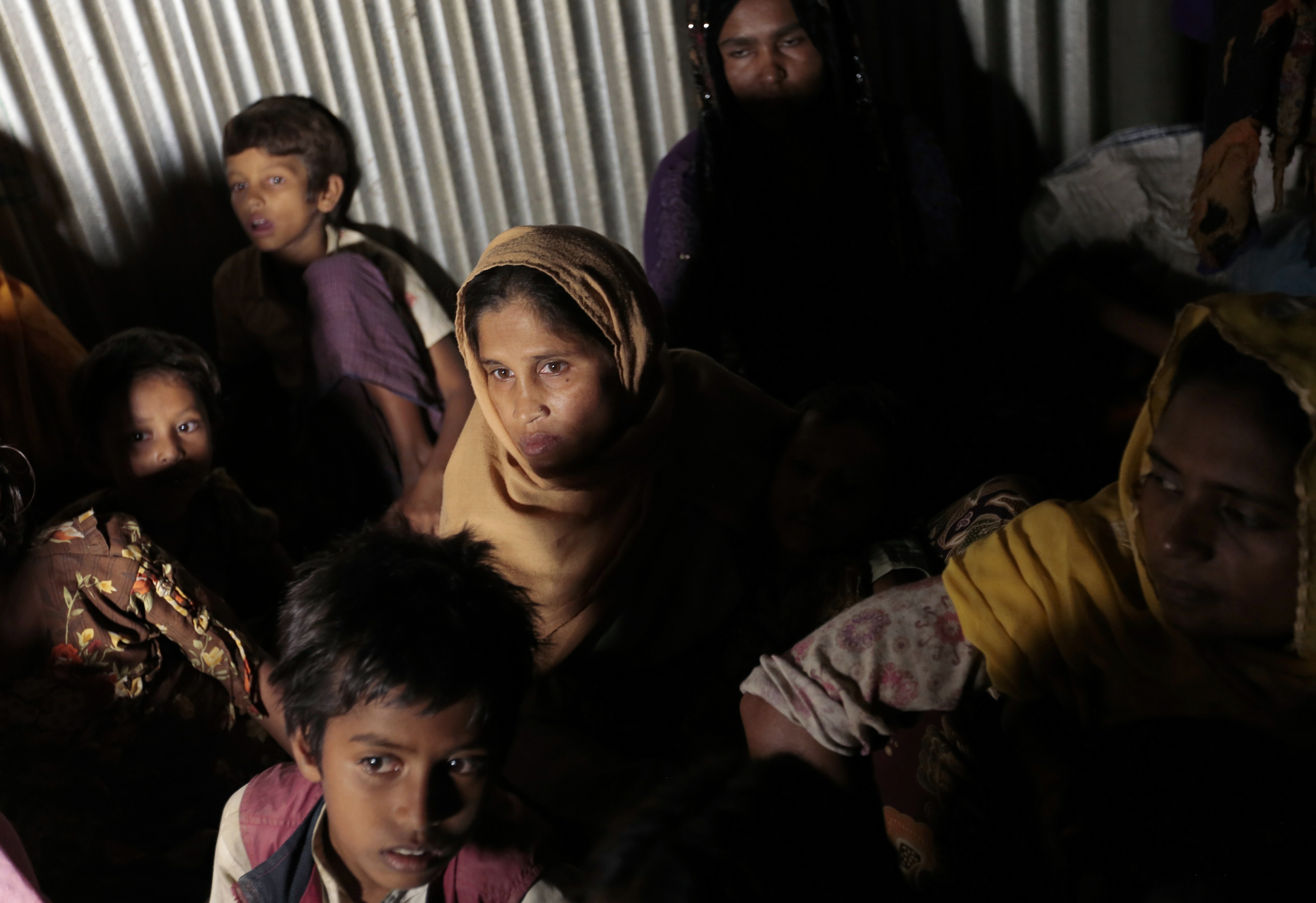 FILE - In this Dec. 2, 2016 file photo, Rohingya from Myanmar who recently crossed over to Bangladesh, huddle in a room at an unregistered refugee camp in Teknaf, near Cox's Bazar, a southern coastal district about, 296 kilometers (183 miles) south of Dhaka, Bangladesh. Muslim villagers in western Myanmar's troubled Rakhine state said Sunday, Jan. 15, 2017, that they hope positive change will result from a U.N. envoy's visit to the region, where soldiers are accused of widespread abuses against minority Muslims, including murder, rape and the burning of thousands of homes. (AP Photo/A.M. Ahad, File)
