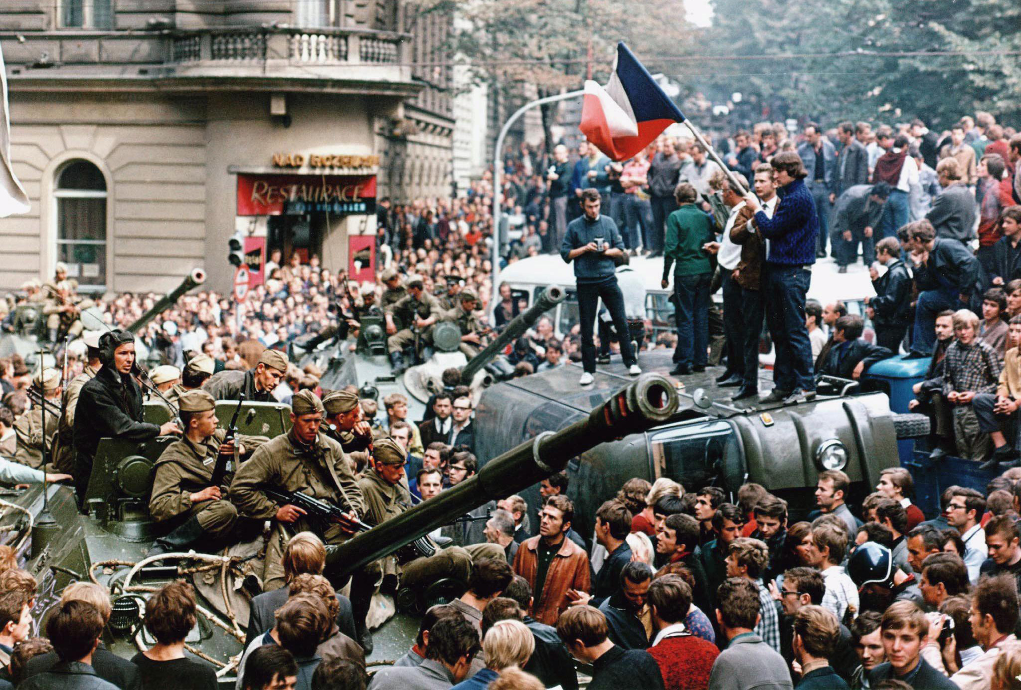 PRAGUE, CZECH REPUBLIC - AUGUST 21:  Czech youngsters holding a Czechoslovak flag stand atop an overturned truck as other Prague residents surround Soviet tanks in  Prague on 21 August 1968 as the Soviet-led invasion by the Warsaw Pact armies crushed the so called Prague Spring reform in former Czechoslovakia.  (Photo credit should read LIBOR HAJSKY/AFP/Getty Images)