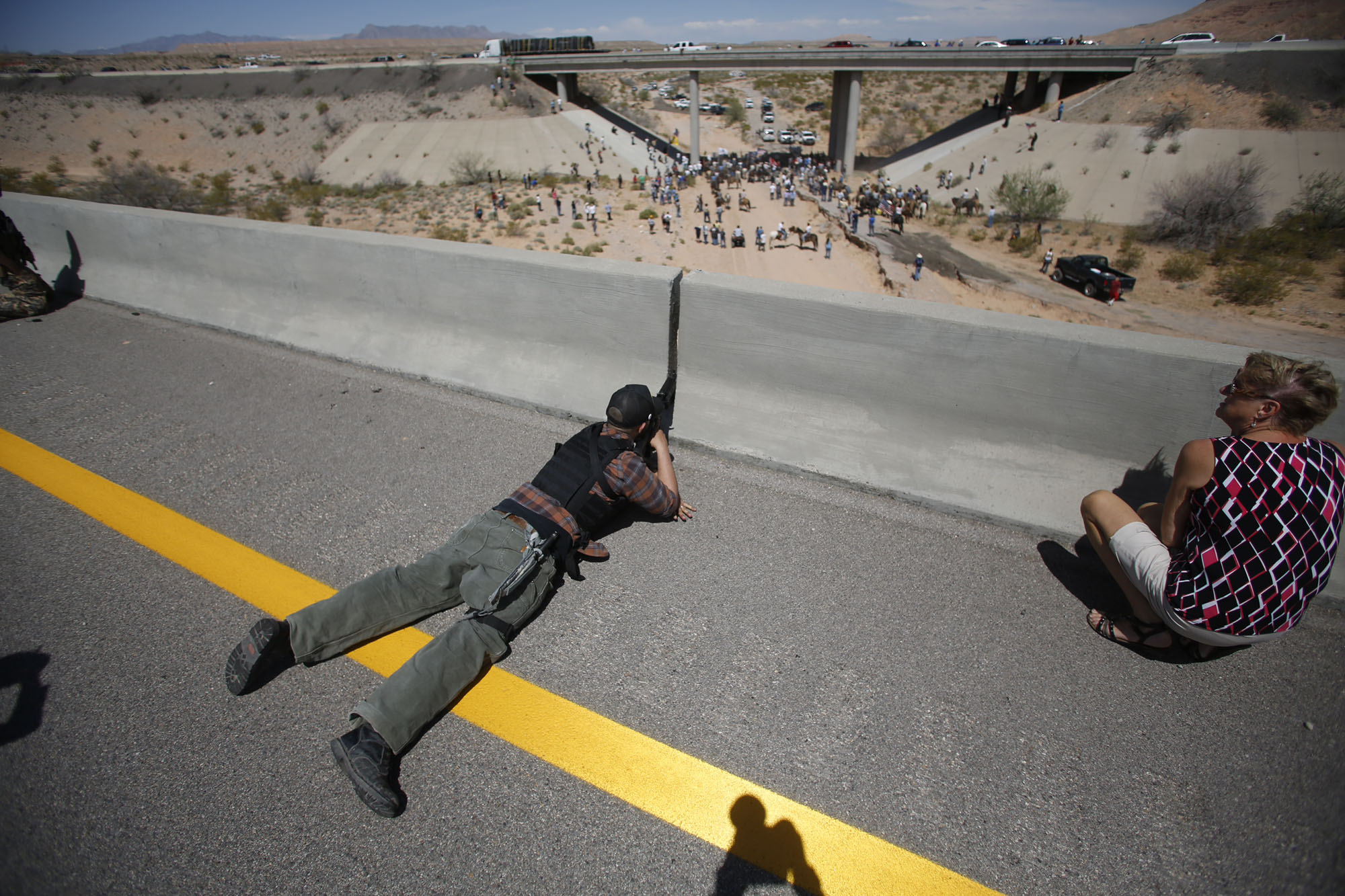 Eric Parker from central Idaho aims his weapon from a bridge as protesters gather by the Bureau of Land Management's base camp, where cattle that were seized from rancher Cliven Bundy are being held, near Bunkerville, Nevada April 12, 2014. The U.S. Bureau of Land Management on Saturday said it had called off an effort to round up Bundy's herd of cattle that it had said were being illegally grazed in southern Nevada, citing concerns about safety. The conflict between Bundy and U.S. land managers had brought a team of armed federal rangers to Nevada to seize the 1,000 head of cattle. REUTERS/Jim Urquhart (UNITED STATES - Tags: ANIMALS CIVIL UNREST AGRICULTURE CRIME LAW) - RTR3L0EB