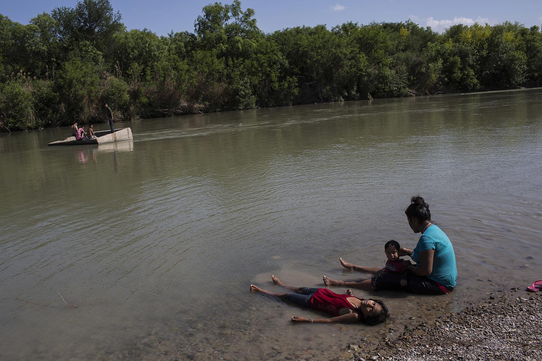 People cool off in the Rio Grand river, or Rio Grande and Rio Bravo in Spanish, in Nuevo Laredo, Tamaulipas state, Mexico, Saturday, March 25, 2017, across the border from Laredo, Texas. (AP Photo/Rodrigo Abd)