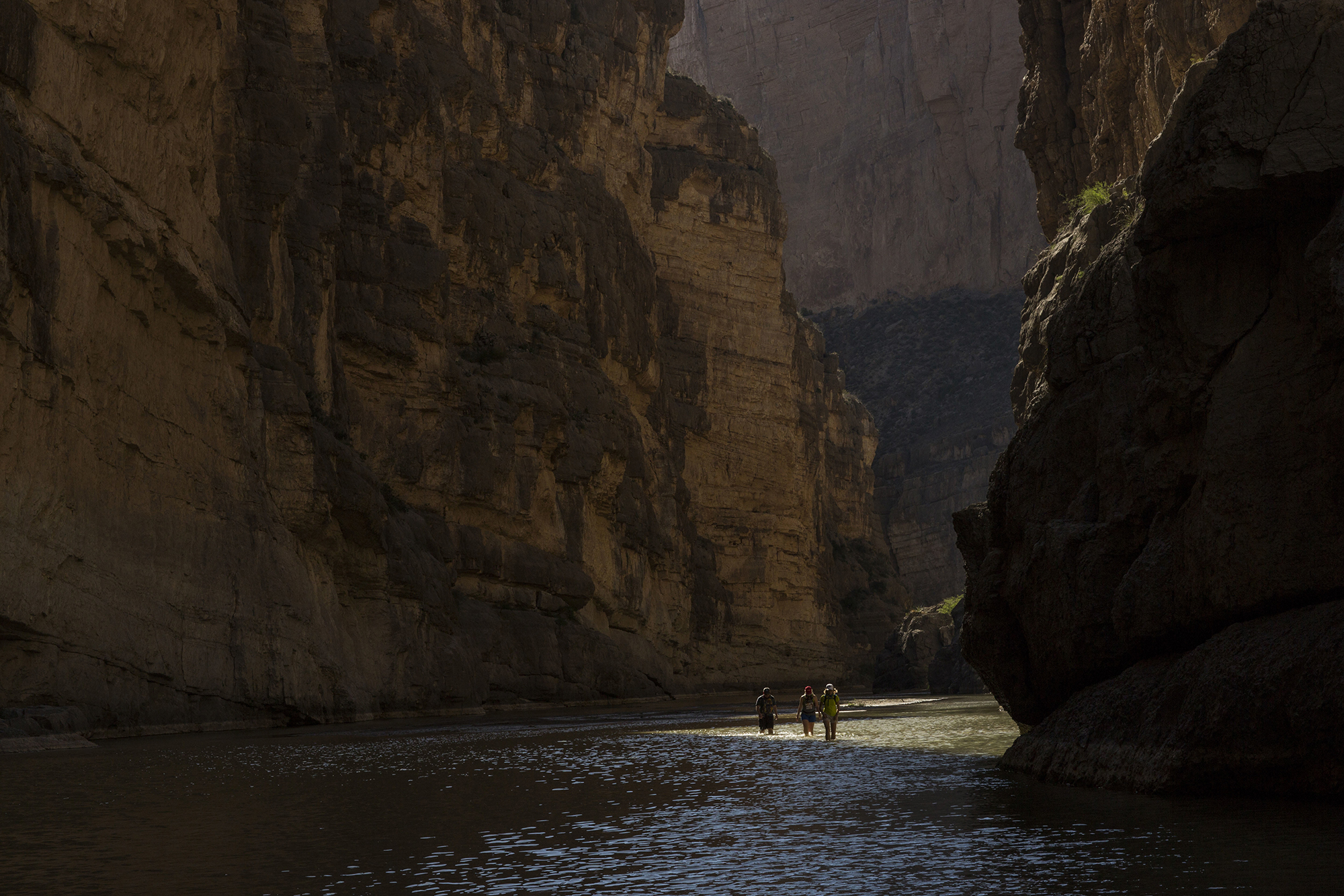 Tourists walk through Santa Elena Canyon, wading through the water of the Rio Grande, between Mexico, left, and the US, right, as they vacation at Big Bend National Park in Texas, Monday, March 27, 2017. Here the Rio Grande slides between two sheer cliff faces, one in Mexico and one in the United States, that tower 1,500 feet above the water. (AP Photo/Rodrigo Abd)