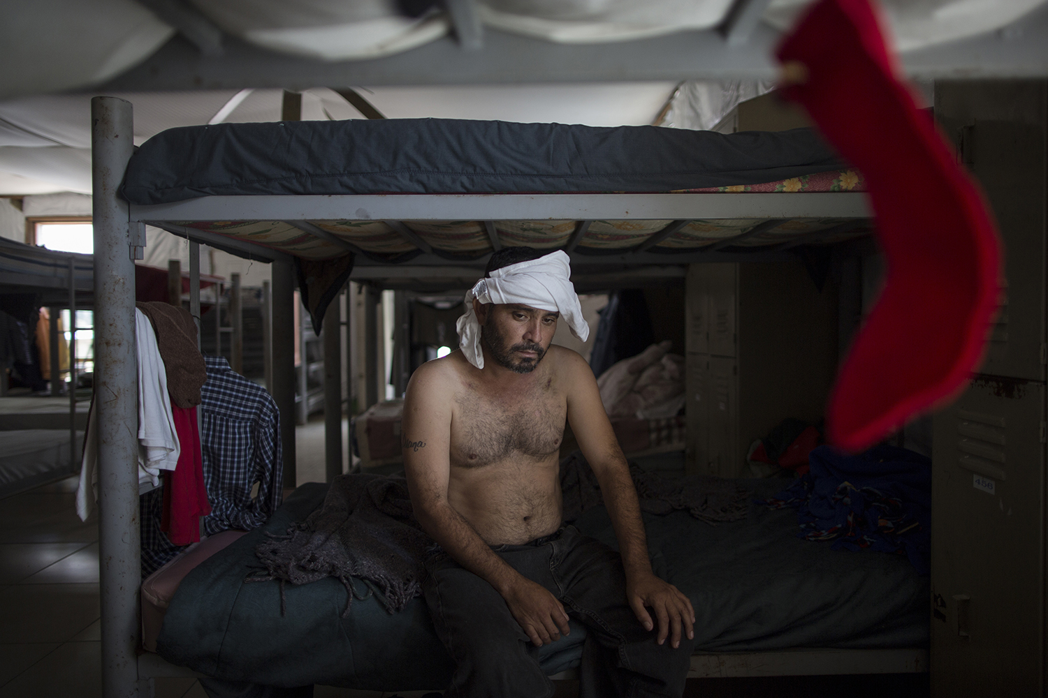 """Delfino Luis Trevino, with his head bandaged, rests on a bunk bed at the """"Senda de Vida"""" migrant shelter in Reynosa, Mexico, Wednesday, March 22, 2017. Trevino, from Veracruz, Mexico, said he was beaten one week ago by """"polleros,"""" the Spanish name for human traffickers on the border, because he tried to cross to McAllen, Texas without hiring them. He said they where charging $500 dollars. (AP Photo/Rodrigo Abd)"""