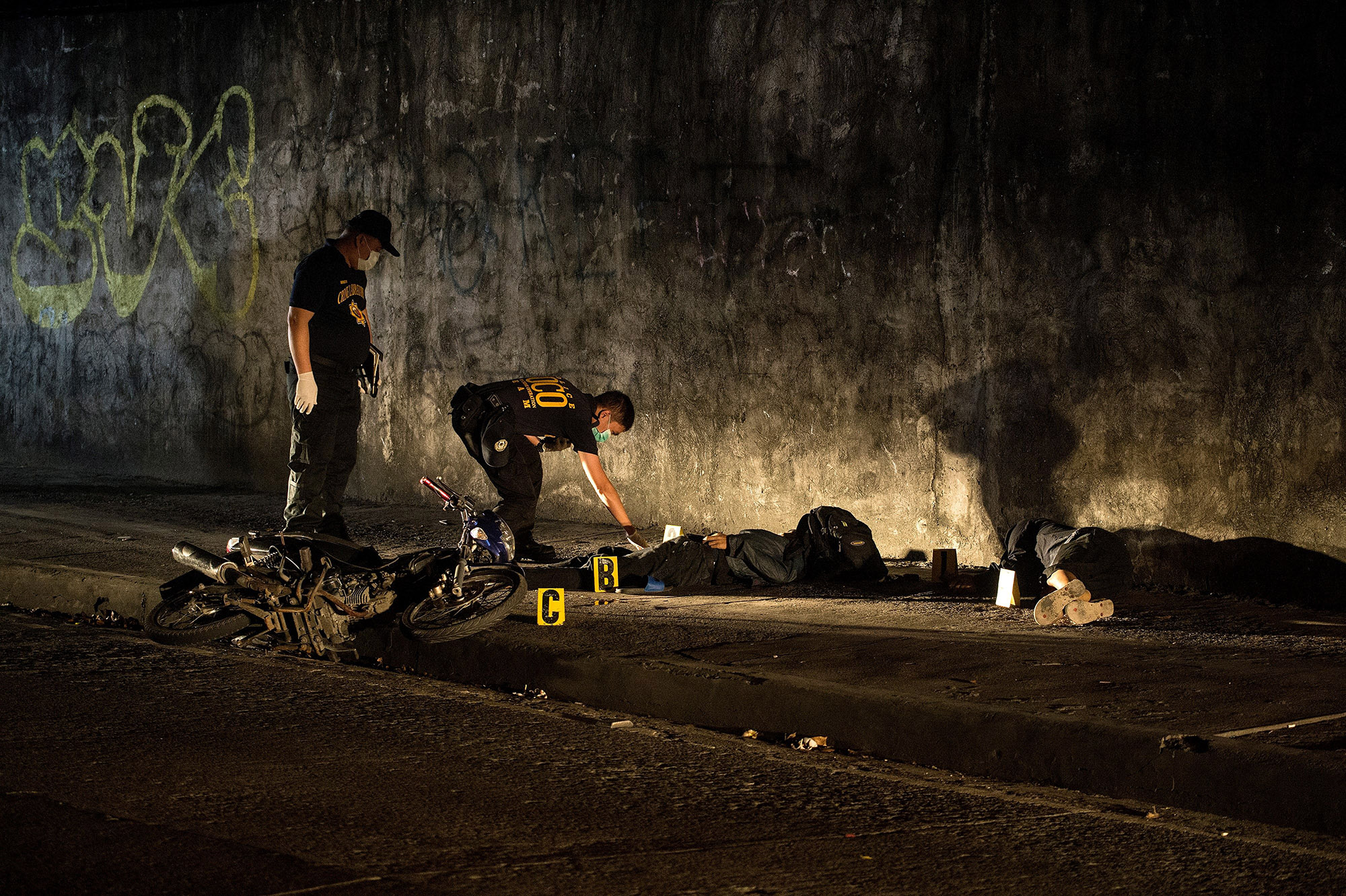 """This picture taken on February 8, 2017 shows a member of a """"Scene of the Crime Operatives (SOCO)"""" team investigating the crime scene where two alleged robbers were killed after a gun fight with police in Manila.<br /><br /><br /><br /><br /><br /> Shadowy assassins have killed scores of poor victims in the Philippines after President Rodrigo Duterte officially ordered police to withdraw from his deadly drug war, a rights monitor said on February 17. / AFP / NOEL CELIS        (Photo credit should read NOEL CELIS/AFP/Getty Images)"""