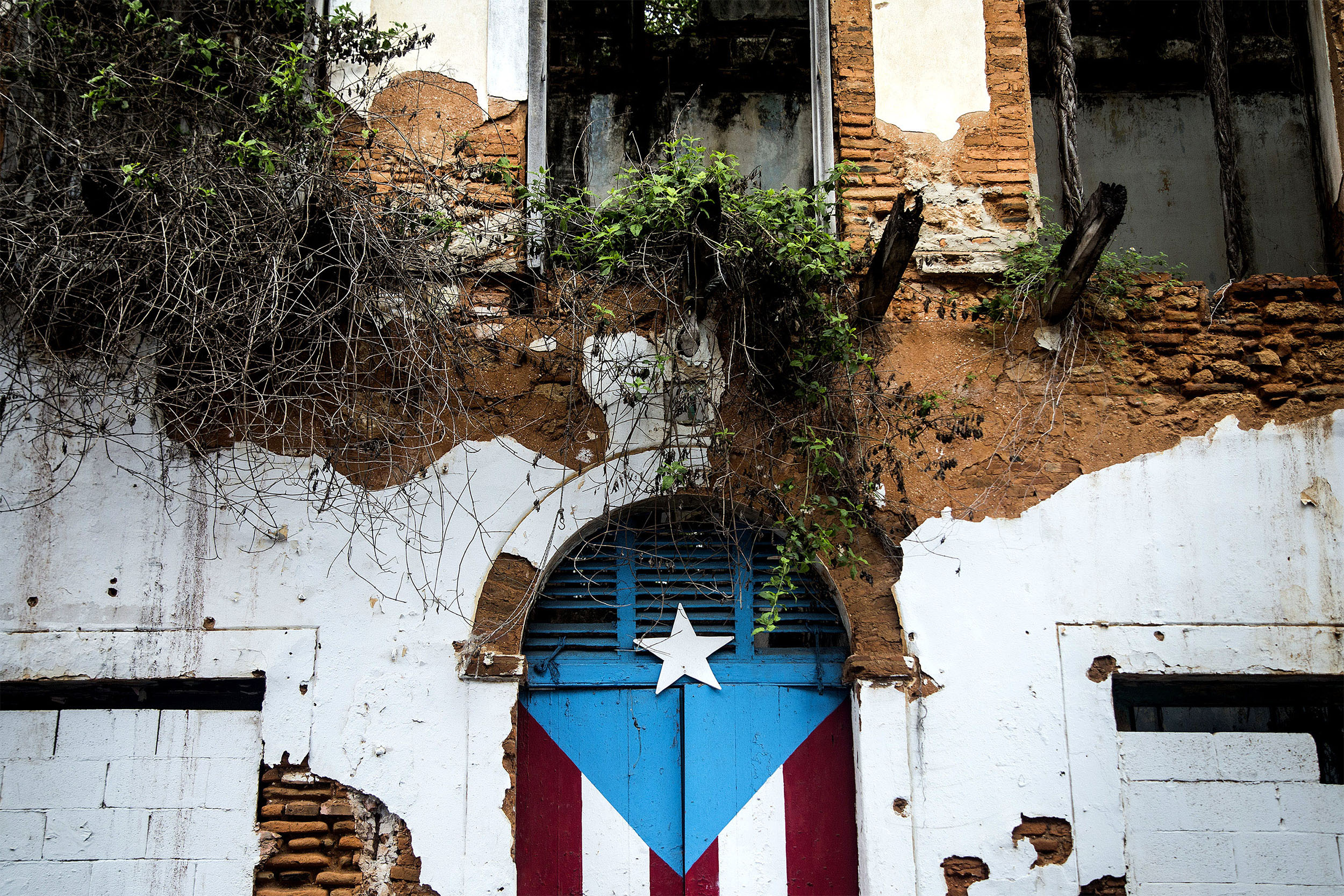 A Puerto Rican flag is painted on the doorway of an abandoned building in San Juan, Puerto Rico, on May 1, 2016.