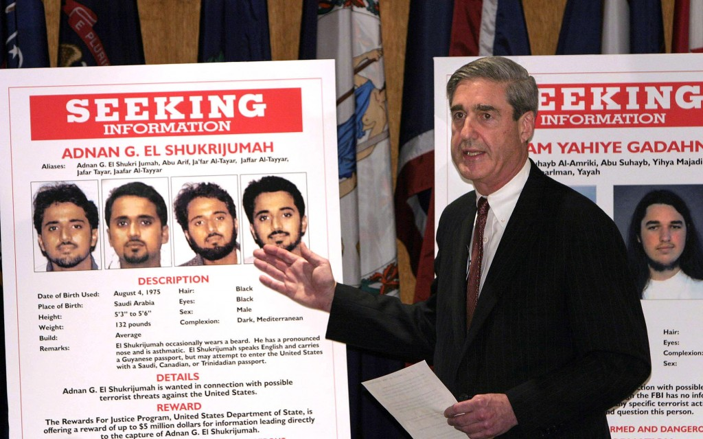 """UNITED STATES - MAY 26:  FBI Director Robert S. Mueller III gestures toward a placard bearing photos of suspected terrorist Adnan G. El Shukrijumah at a news conference in Washington, DC on Wednesday, May 26, 2004. The U.S. has """"credible intelligence from multiple sources"""" that al-Qaeda plans to attack the U.S. in the next few months, Attorney General John Ashcroft said.  (Photo by Dennis Brack/Bloomberg via Getty Images)"""