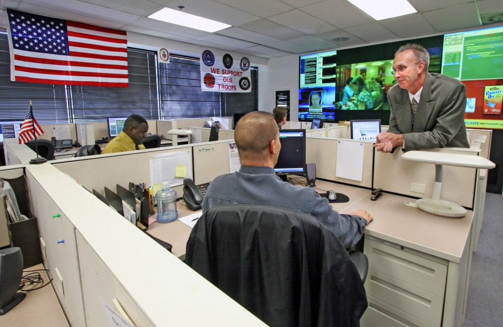 "UNITED STATES - NOVEMBER 02: Maryland state ""fusion center,"" where federal and local officials share info about possible terrorist activities. Photo taken in the Watch Center where all terrorism and suspicious calls are routed. On the right is Jeffrey L. Wobbleton, Maryland Coordination and Analysis Center Watch Commander speaking with one of the working specialists. (Photo by Robert A. Reeder/Washington Post/Getty Images)"