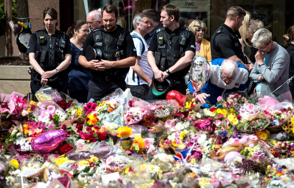 Police officers join members of the public to view the flowers and messages of support in St Ann's Square in Manchester, northwest England on May 31, 2017, placed in tribute to the victims of the May 22 terror attack at the Manchester Arena. / AFP PHOTO / OLI SCARFF        (Photo credit should read OLI SCARFF/AFP/Getty Images)