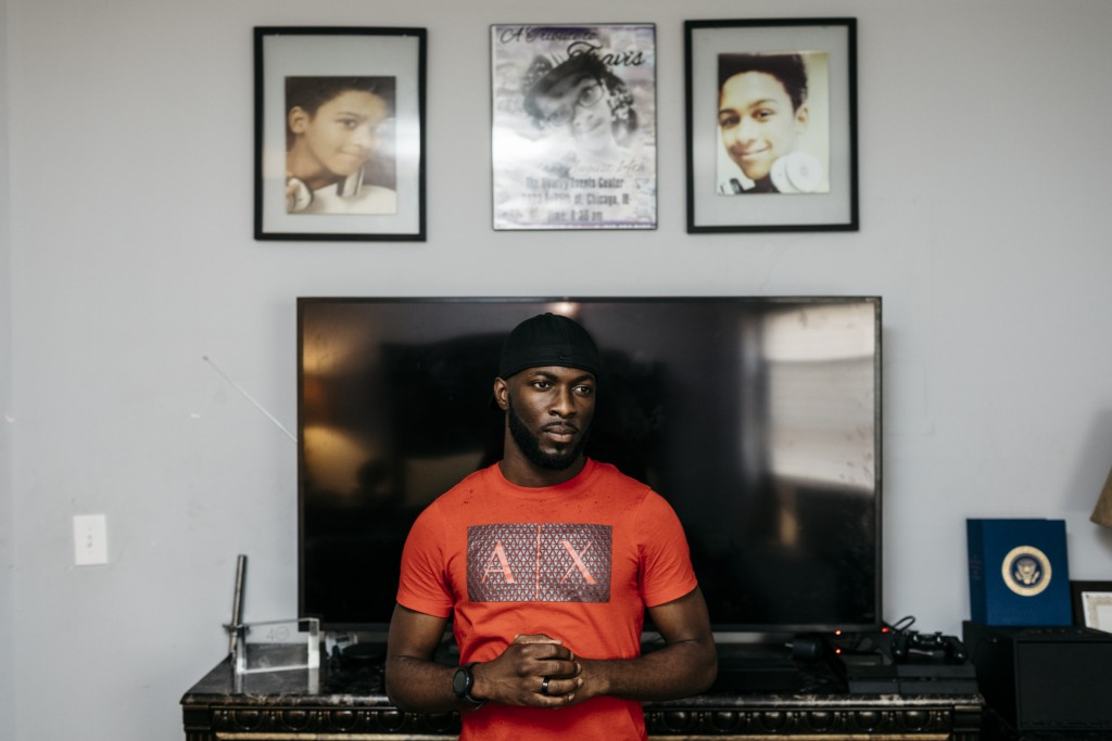 Chicago, IL - July 13, 2017 - Jedediah Brown stands in his bedroom in the South Shore neighborhood of Chicago. Memorial photos of his cousin, who he says he raised like a son, hang on the wall above his television.