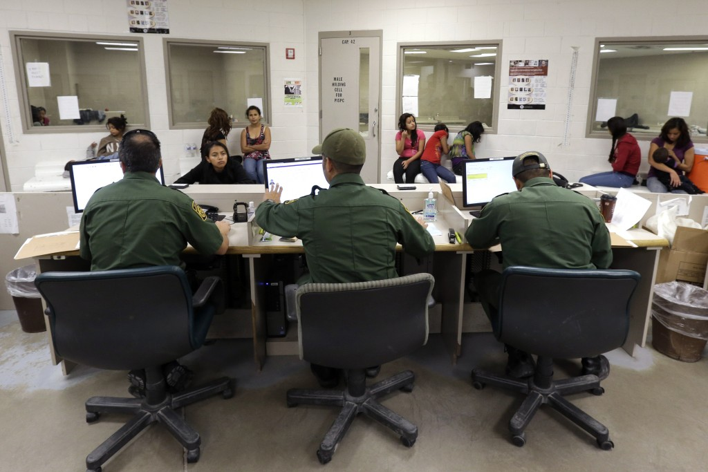 FILE - This June 18, 2014 file photo shows U.S. Customs and Border Protection agents working at a processing facility in Brownsville,Texas. Immigration courts are speeding up hearings for the tens of thousands of Central American children caught on the U.S. border after criticism that the backlogged system is letting immigrants stay in the country for years while waiting for their cases to be heard. (AP Photo/Eric Gay, Pool)