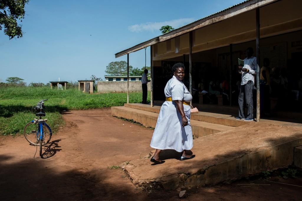 Filder Akello, a nurse midwife, enters another health facility on March 27, 2018 in Bobi, Uganda.