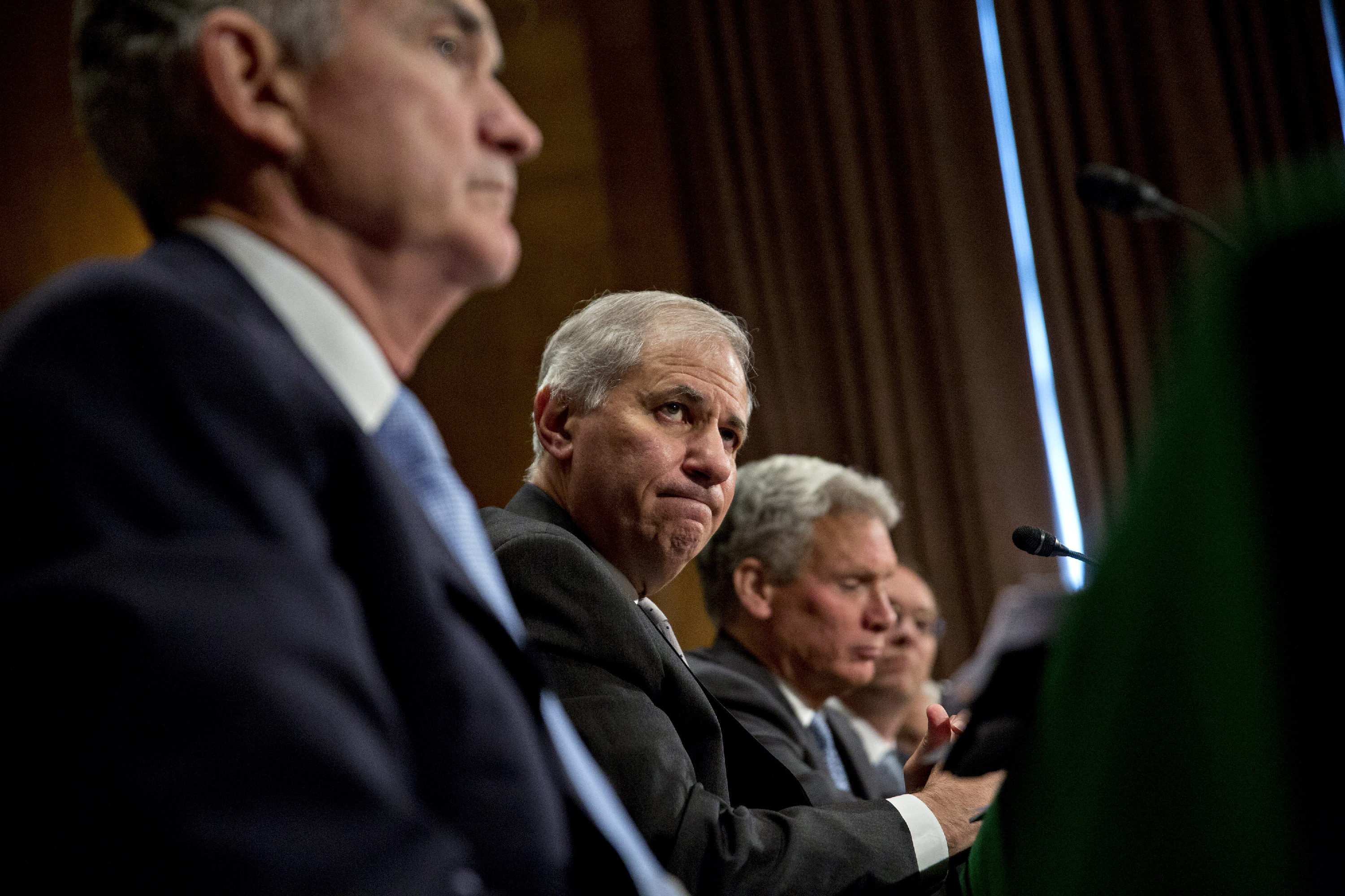 Martin Gruenberg, chairman of the Federal Deposit Insurance Corp. (FDIC), center, and Jerome Powell, governor of the U.S. Federal Reserve, left, listen during a Senate Banking Committee hearing in Washington, D.C., U.S., on Thursday, June 22, 2017. Top U.S. banking regulators are sprinting to ease the Volcker Rule, stress tests and other constraints on Wall Street after the Trump administration issued a long list of proposals last week for rolling back post-crisis financial rules. Photographer: Andrew Harrer/Bloomberg via Getty Images