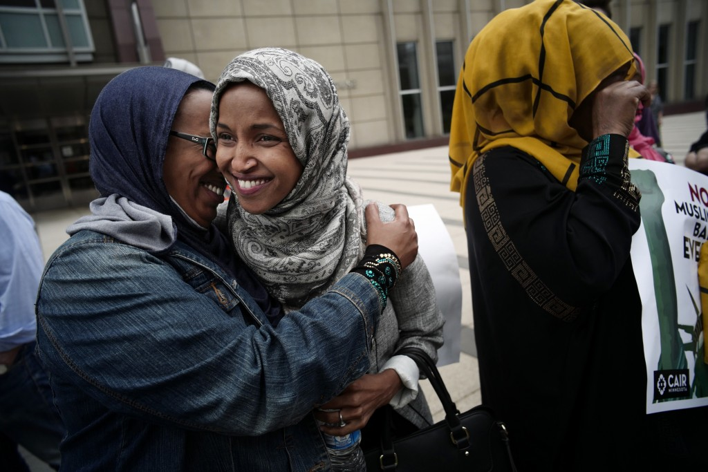 State Rep. Ilhan Omar, second left, a Minneapolis Democrat running for the U.S. House, is hugged after her moving speech against the Muslim ban Tuesday, June 26, 2018, in Minneapolis. Muslim individuals and groups, as well as other religious and civil rights organizations, expressed outrage and disappointment at the U.S. Supreme Court's decision Tuesday to uphold President Donald Trump's ban on travel from several mostly Muslim countries. (Richard Tsong-Taatarii/Star Tribune via AP)