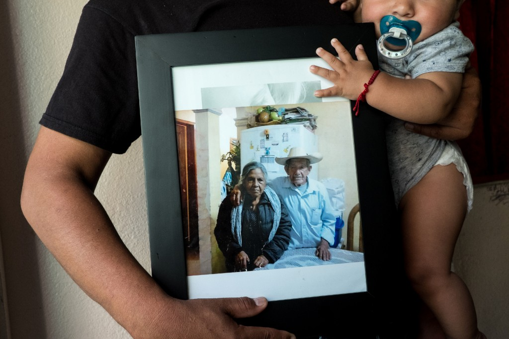 Carlos Rueda Cruz, 28, holds his son Santiago, 8 months old, as he poses with a photograph of his grandparents Maria de Jesus Peña Loza, left, and Pedro Rueda, right, inside his home in Sacramento, Calif., Monday, Sept. 10, 2018. Rueda Cruz's grandfather raised him as he grew up in Michoacán, Mexico. (Joel Angel Juárez for The Intercept)