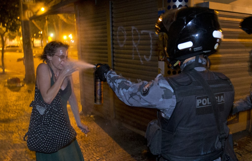 FILE - A military police peper sprays a protester during a demonstration in Rio de Janeiro, Brazil, Monday, June 17, 2013. Brazil has seen almost daily protests in the weeks leading up to the World Cup. Last year, huge anti-government protests took over streets in dozens of cities during the Confederations Cup, which is international soccer's warm-up tournament for its premier event, the World Cup. (AP Photo/Victor R. Caivano, File)
