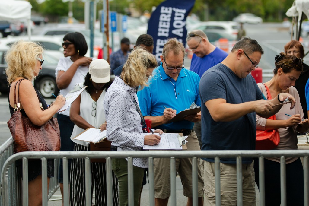 Voters arrive for early voting at the Gwinnett County (Ga.) Voter Registrations and Elections Office in Lawrenceville, Ga., on Wednesday, Oct. 17, 2018. Here, voters fill out paperwork prior to entering the building Photo by Kevin D. Liles for The Intercept