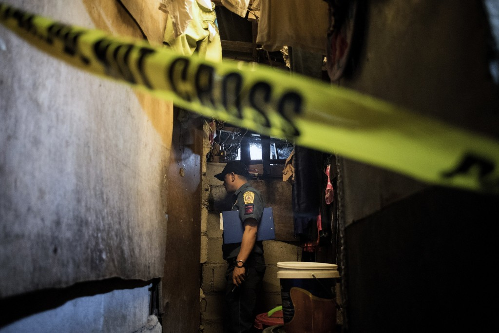 """A policeman investigates the scene where the body of an alleged drug user lies dead at a slum area in Manila after unidentified assailants killed him on December 8, 2017. Philippine President Rodrigo Duterte on December 5 told human rights groups criticising his deadly anti-drug war to """"go to hell"""" after ordering police back to the frontlines of the crackdown. Duterte had removed the police less than two months ago in response to rising opposition to the campaign. But his spokesman said he was now reinstating them because drug crimes had risen in their absence. / AFP PHOTO / NOEL CELIS        (Photo credit should read NOEL CELIS/AFP/Getty Images)"""