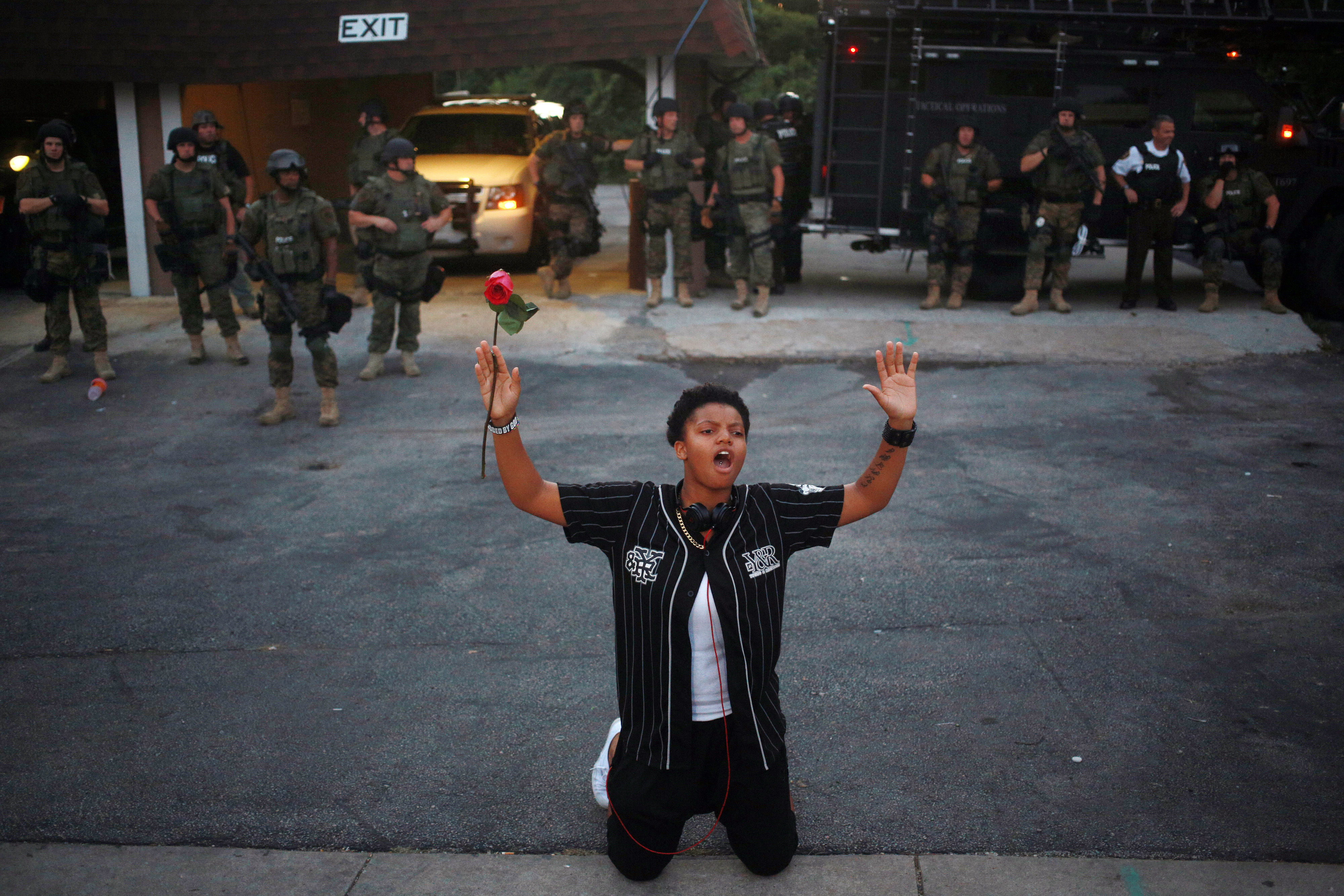 Bloomberg's Best Photos 2014: A demonstrator holding a red rose kneels in front of armed police officers and raises their hands above her head during protests in Ferguson, Missouri, U.S., on Tuesday, Aug. 19, 2014. A grand jury will begin hearing evidence tomorrow in the police shooting death of Ferguson, Missouri, teenager Michael Brown, as violent clashes continued in the St. Louis suburb. Photographer: Luke Sharrett/Bloomberg via Getty Images