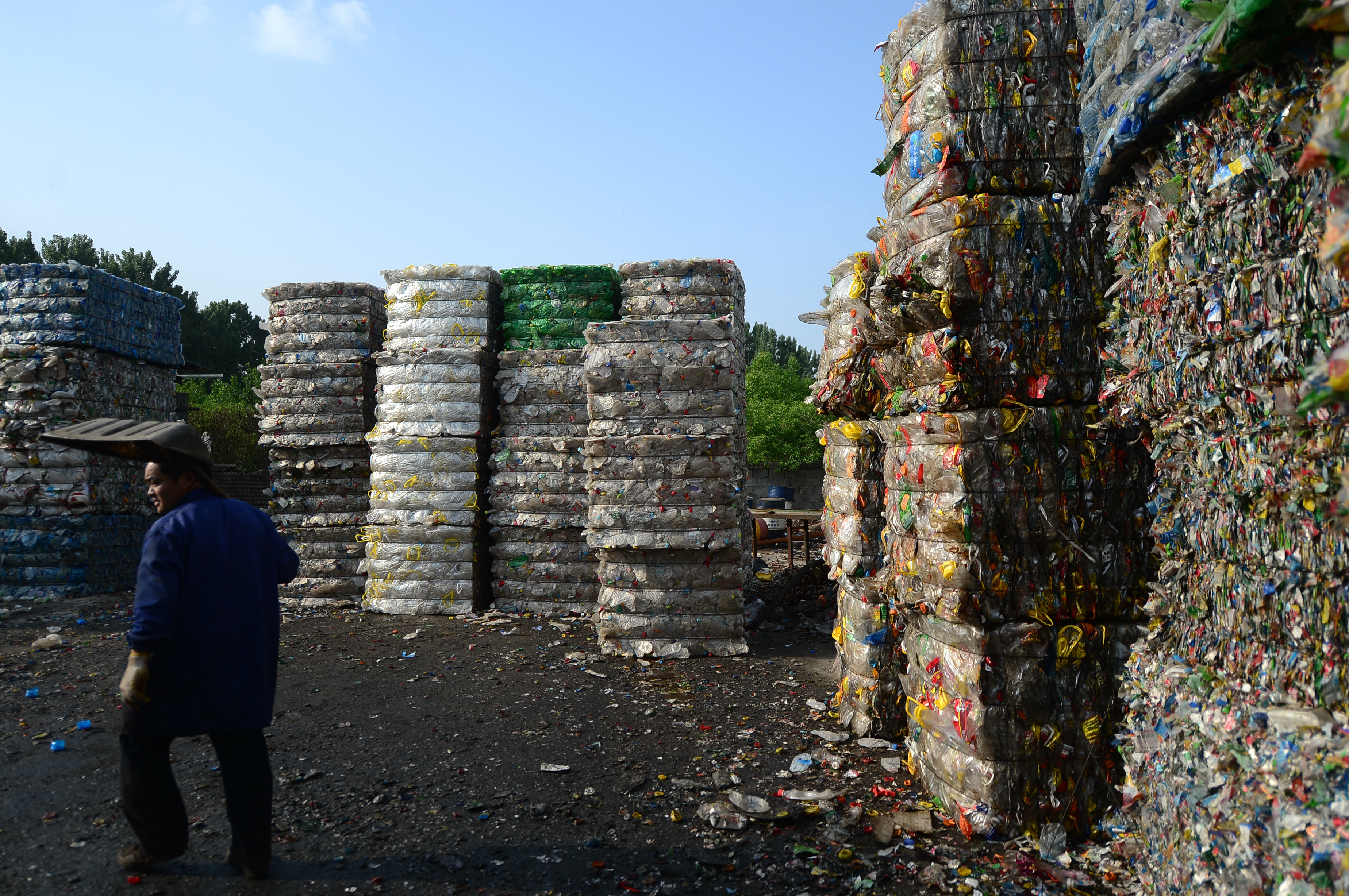 A Chinese worker labors in front of high piles of plastic bottles at the plastic bottle recycling station, which trapped a man, in Ji'nan city, east China's Shandong province, 4 May 2017.