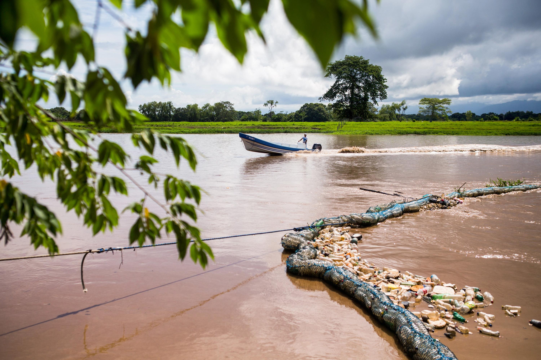 """Os moradores de El Quetzalito são encarregados de manter as """"biocercas"""" recentemente instaladas pelo governo, que atuam como barreiras superficiais para impedir que o lixo flutuante chegue à foz do rio ao desaguar no Caribe."""