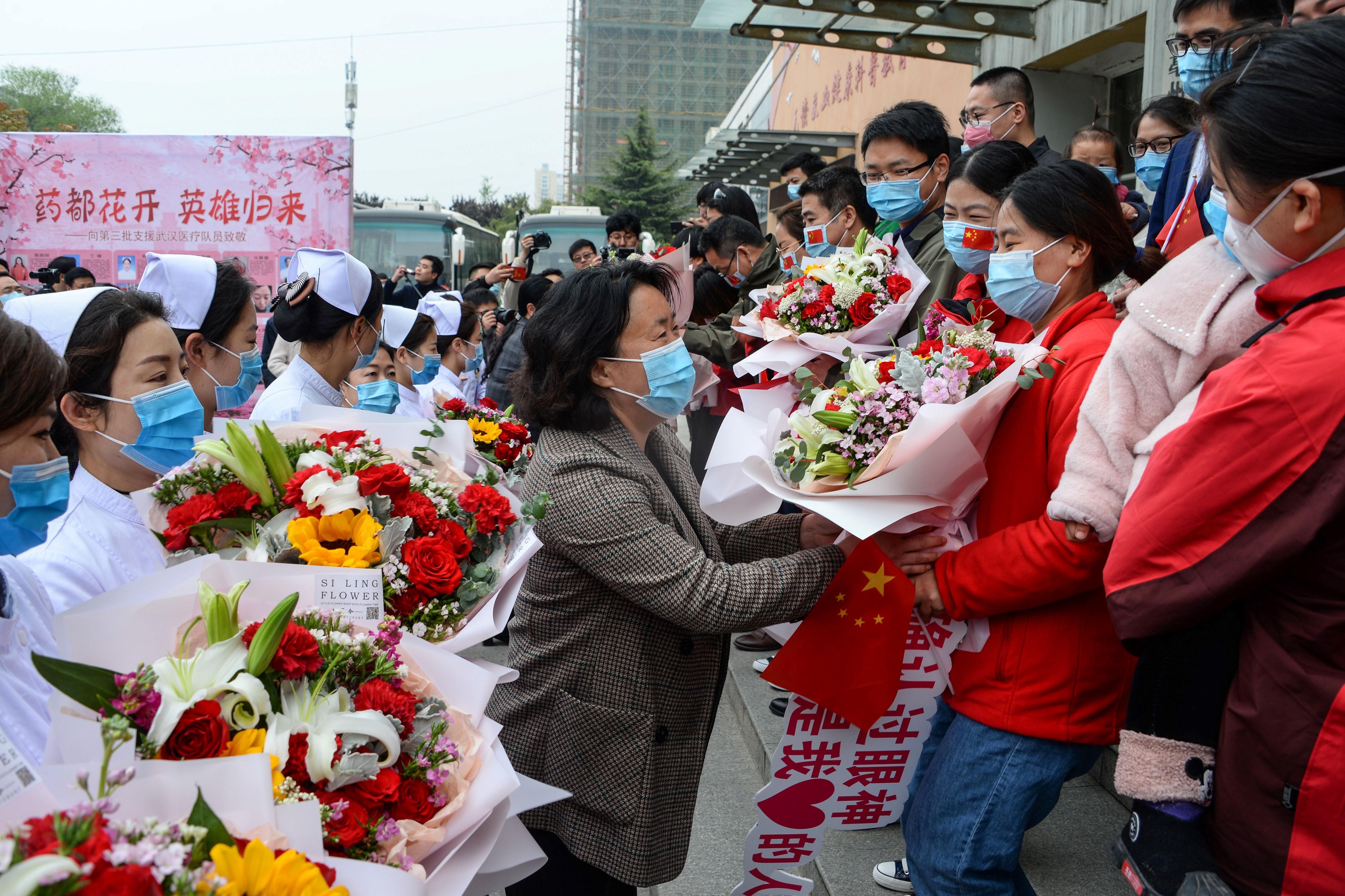 Após ajudarem no esforço de combate à covid-19 em Wuhan, membros da equipe médica recebem flores ao voltar para casa em Bozhou, na província chinesa de Anhui, em 10 de abril de 2020.