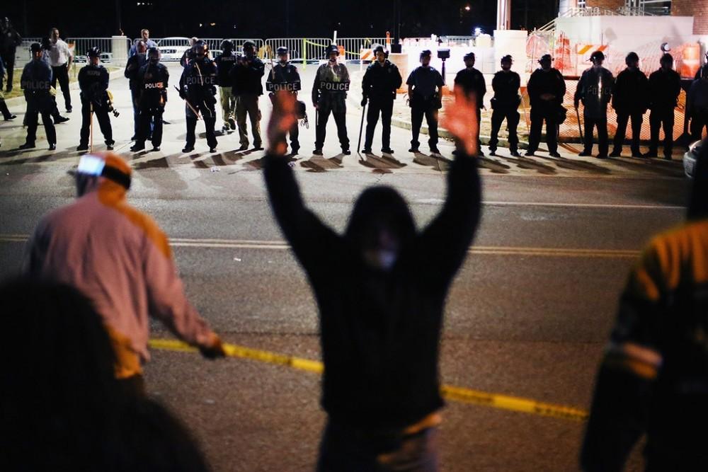 Policiais se posicionam diante de manifestantes em frente a uma delegacia, em meio aos protestos pela morte de Michael Brown, 18 anos, em 22 de outubro de 2014, em Ferguson, Missouri