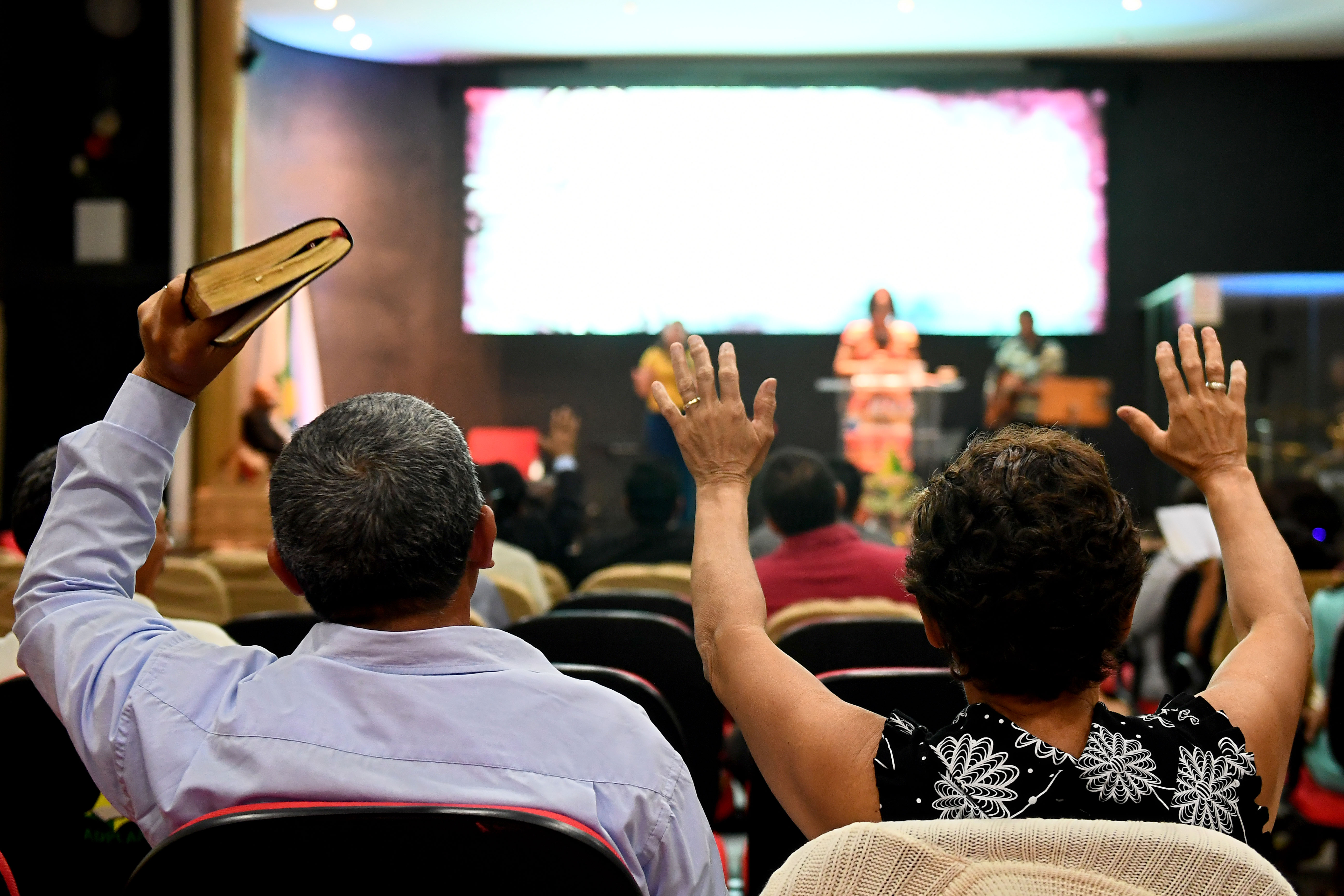 Faithful pray at an evangelical church in Brasilia, on September 21, 2018 for the recovery of the health of Brazilian right-wing presidential candidate Jair Bolsonaro, who suffered a knife attack during the campaign. - The powerful evangelical churches of Brazil are increasingly permeable to the rhetoric of the Brazilian right-wing presidential candidate Jair Bolsonaro. In the latest poll taken by Datafolha, Bolsonaro led with 28 percent ahead of leftist candidate Fernando Haddad on 16. Harvesting 36% of adhesions among evangelical voters, more than twice that of any of the other candidates (Fernando Haddad, 12%; Geraldo Alckmin, 10%, Ciro Gomes, 10%, Marina Silva, 8%). (Photo by EVARISTO SA / AFP)        (Photo credit should read EVARISTO SA/AFP via Getty Images)