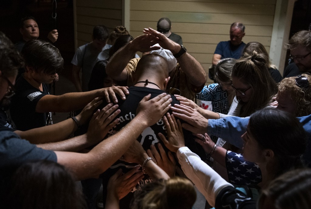 """A group gathers around Patriot Prayer leader Joey Gibson for a prayer after a candlelight vigil Saturday, Sept. 5, 2020, in Vancouver, Wash., for Aaron """"Jay"""" Danielson, who was fatally shot in Portland, Ore."""