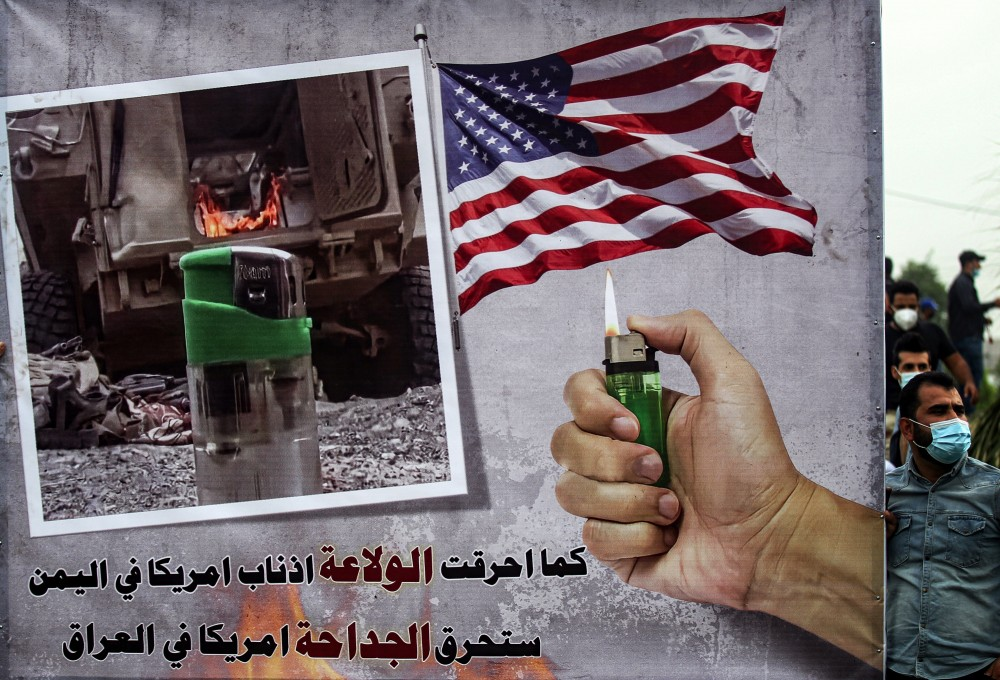 """A sign depicting a hand holding a lighter beneath a US flag and next to a photo of a lighter near a military armoured vehicle with text reading in Arabic """"as the lighter burned the followers of America in Yemen, the lighter will burn America in Iraq"""" is seen during a demonstration by supporters of the Iran-backed Hashed al-Shaabi (Popular Mobilisation) paramilitary forces outside the entrance to the Iraqi capital Baghdad's highly-fortified Green Zone on November 7, 2020, demanding the departure of remaining US forces from Iraq. - Several hundred protesters gathered in the Iraqi capital on Saturday afternoon to demand US troops leave the country in accordance with a parliament vote earlier this year. (Photo by Ahmad AL-RUBAYE / AFP) (Photo by AHMAD AL-RUBAYE/AFP via Getty Images)"""