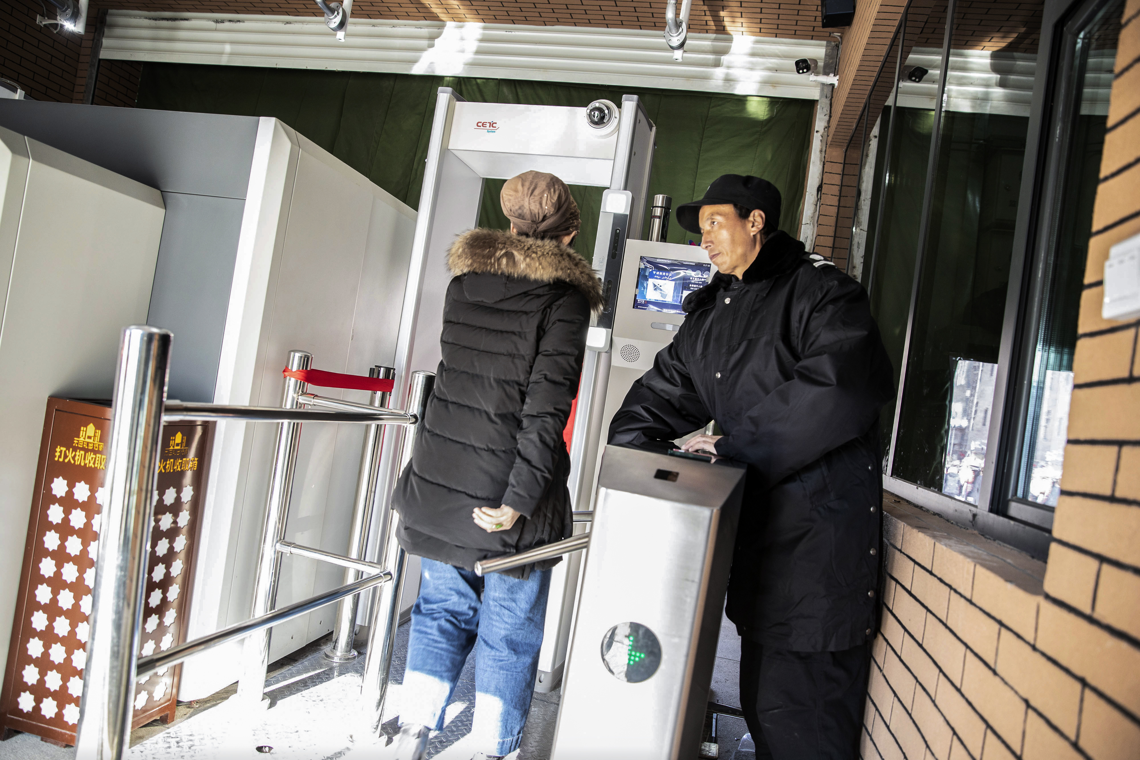 A security officer looks on as a woman passes through a checkpoint, equipped with a metal detector and facial recognition technology, to enter the main bazaar in Urumqi, Xinjiang autonomousregion, China, on Tuesday, Nov. 6, 2018. Although it represents just 1.5 percent of China's population and 1.3 percent of its economy, Xinjiang sits at the geographic heart of Xi's signature Belt and Road Initiative. Source: Bloomberg