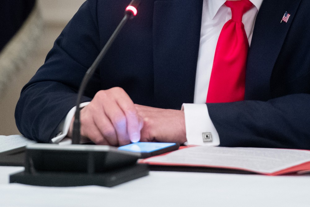 US President Donald Trump uses his cellphone as he holds a roundtable discussion with Governors about the economic reopening of closures due to COVID-19, known as coronavirus, in the State Dining Room of the White House in Washington, DC, June 18, 2020. (Photo by SAUL LOEB / AFP) (Photo by SAUL LOEB/AFP via Getty Images)