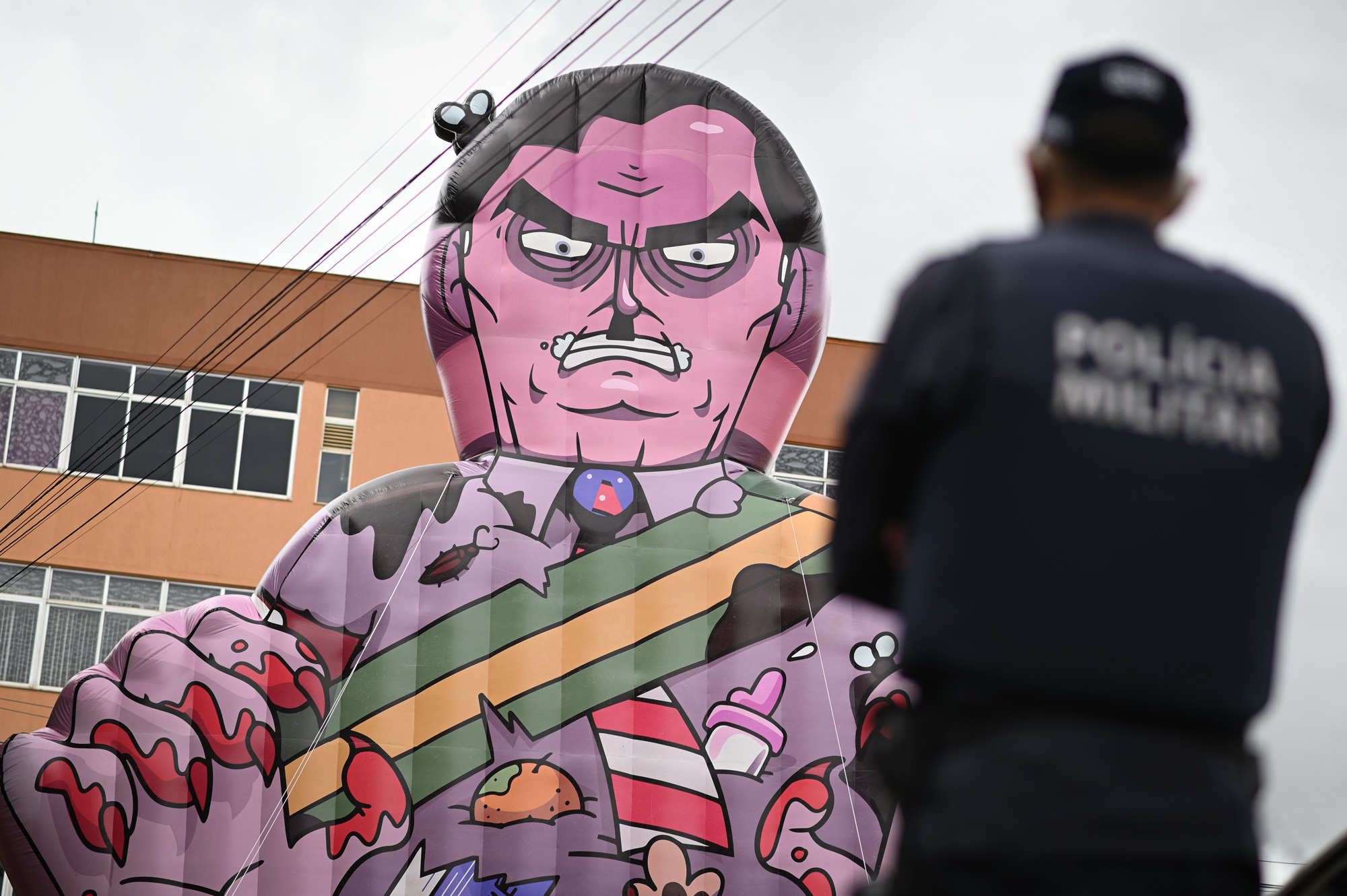 BRASILIA, BRAZIL -JANUARY17: A police officer watches a large puppet representing Brazil's President Jair Bolsonaro as a killer raised by demonstrators during a protest in favor of Bolsonaro's impeachment in front of the headquarters of Brazil's health agency ANVISA (National Health Surveillance Agency) amidst the Coronavirus (COVID - 19) pandemic on January 17, 2021 in Brasilia.Brazil has over 8.455,000 confirmed positive cases of Coronavirus and has over 209,296 deaths. (Photo by Andre Borges/Getty Images)