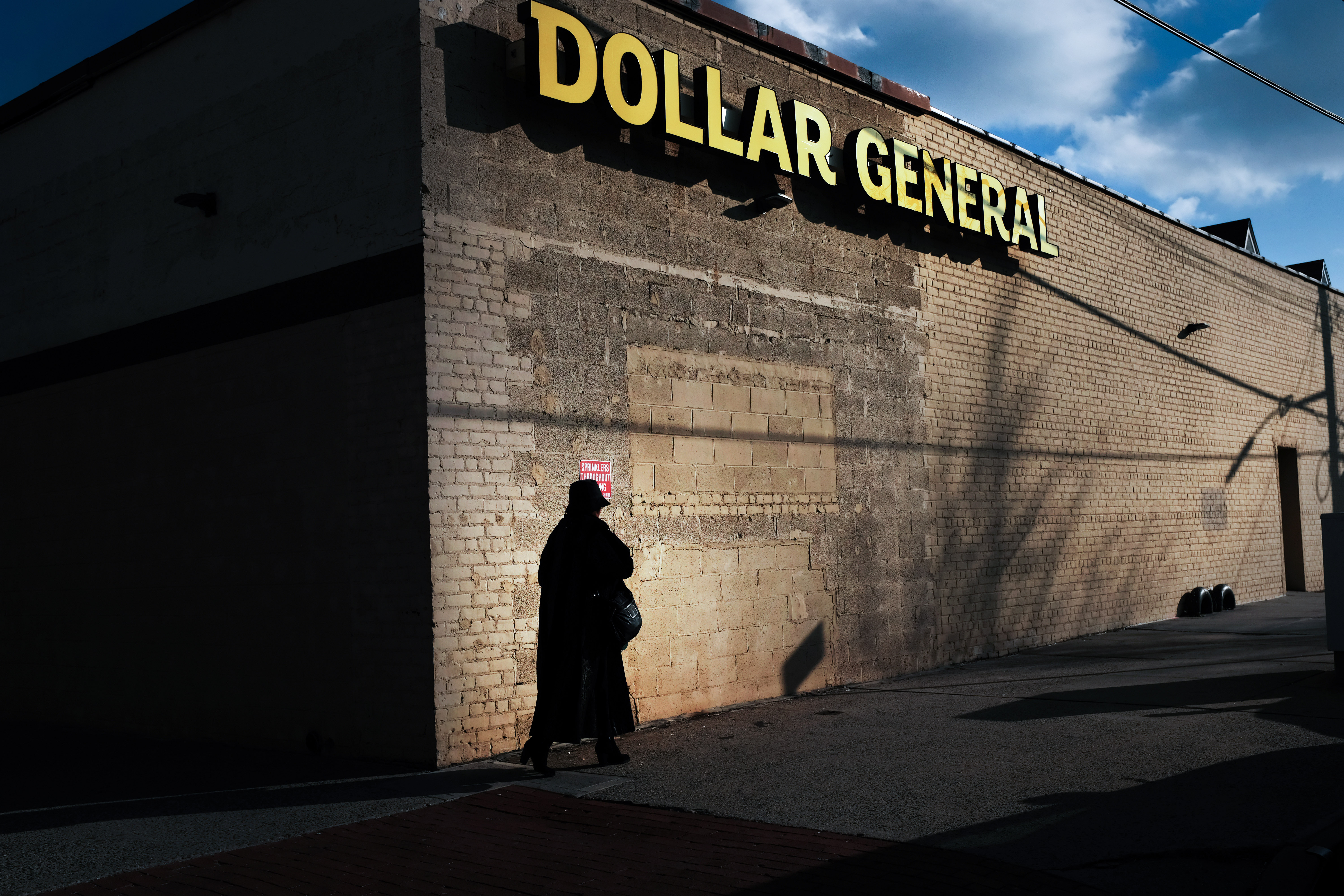 A woman walks by a Dollar General store on December 11, 2018 in the Brooklyn borough of New York City.