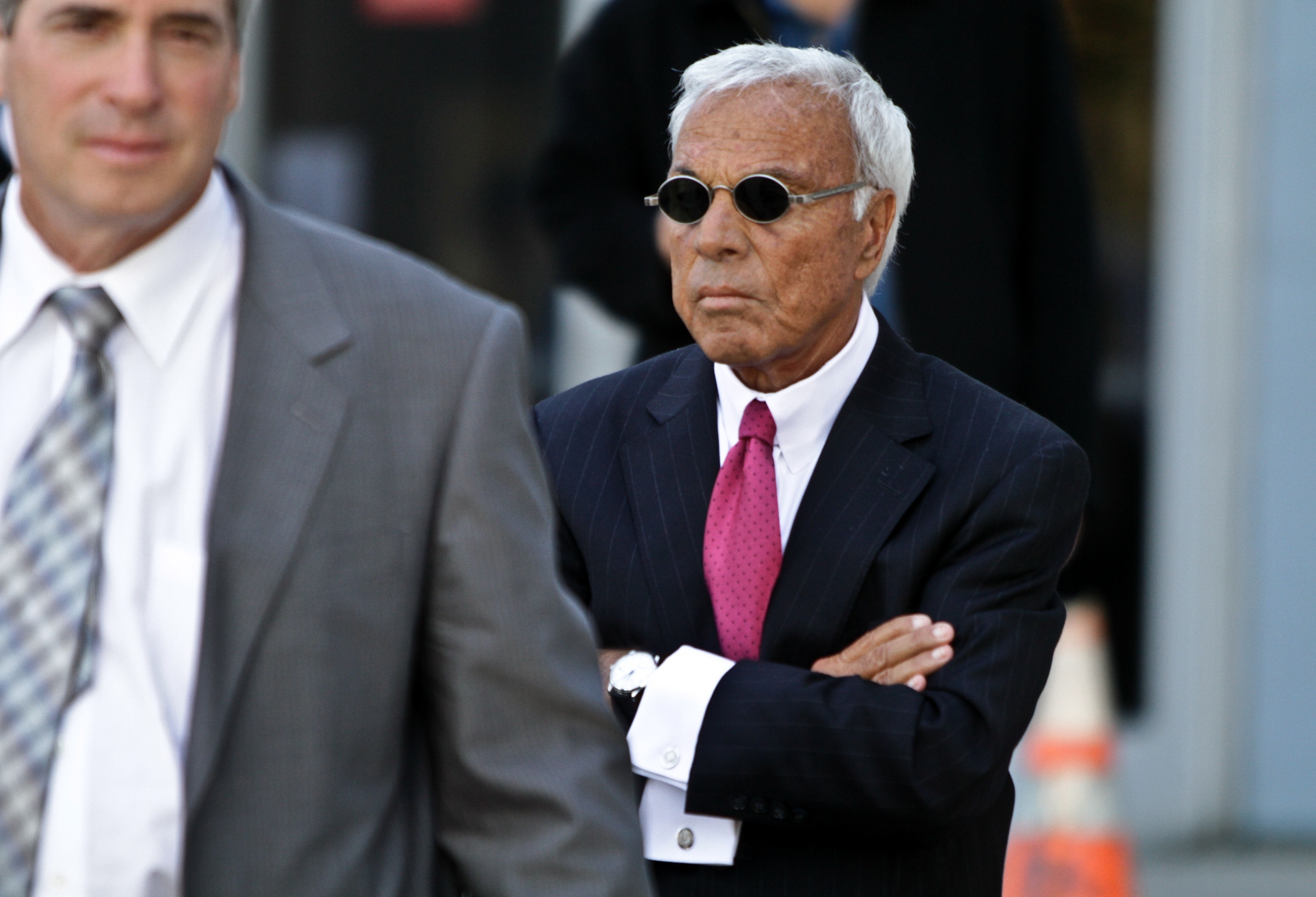 Countrywide Financial former Chief Executive Officer Angelo Mozilo, in dark glasses, emerges from Superior Court in Van Nuys, after testifying in the wrongful dismissal suit of a formal top executive of Countrywide Financial on January 18, 2010 in Van Nuys, CA.