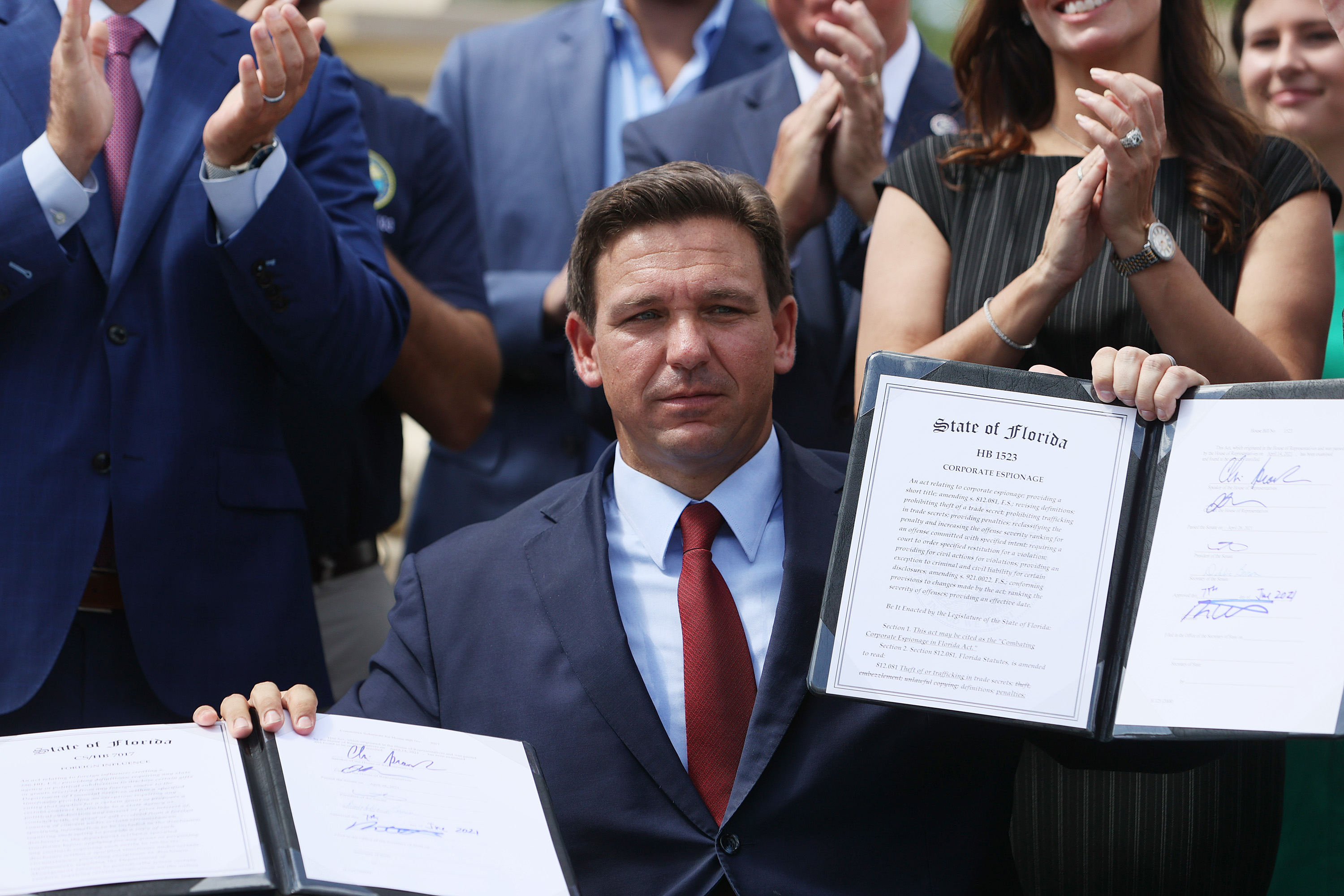 MIAMI, FLORIDA - JUNE 07: Florida Gov. Ron DeSantis holds up two bills he signed at the Florida National Guard Robert A. Ballard Armory on June 07, 2021 in Miami, Florida. The governor signed the bills to combat foreign influence and corporate espionage in Florida from governments like China. (Photo by Joe Raedle/Getty Images)