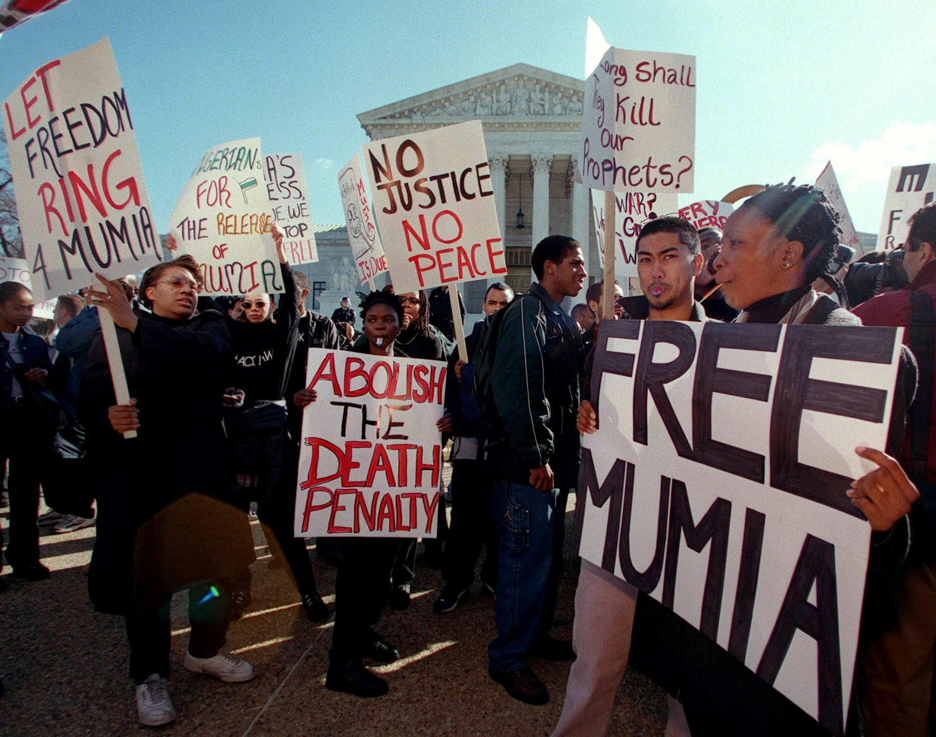 Protesters march with signs calling for the end of the death penalty during a demonstration 28 February, 2000 in front of the US Supreme Court in Washington, DC, as justices inside the Supreme Court hear arguments on the Effective Death Penalty Act of 1996, giving the right to appeal when there is new evidence of innocence. The protesters are seeking a new trial for former radio journalist and one time Black Panther Mumia Abu-Jamal who was sentenced to death for killing a Philadelphia police officer in 1981.    AFP PHOTO/Chris KLEPONIS (Photo credit should read CHRIS KLEPONIS/AFP via Getty Images)