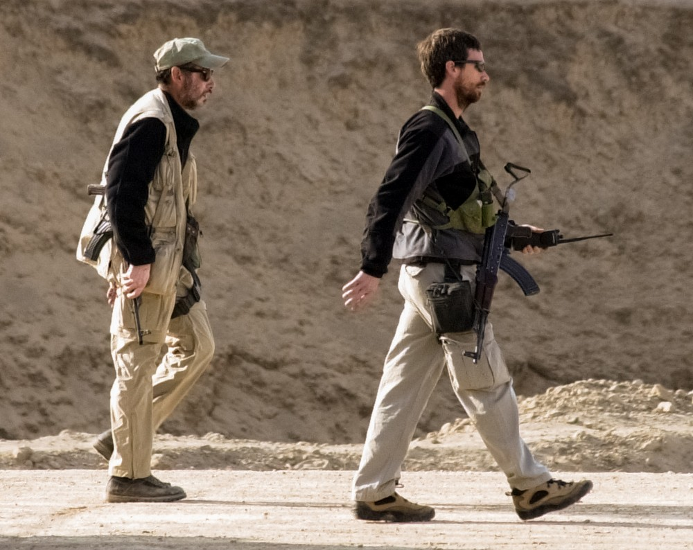 FILE - In this Nov. 27, 2001, file photo two men with U.S. Special Operations forces walk nearby as the Northern Alliance troops fight pro-Taliban forces in the fortress near Mazar-e-Sharif, Northern Afghanistan. The Central Intelligence Agency together with U.S. special operations were the first Americans into Afghanistan after the attacks of Sept. 11th, and will likely be the last U.S. forces to leave.  (AP Photo/Darko Bandic, File)